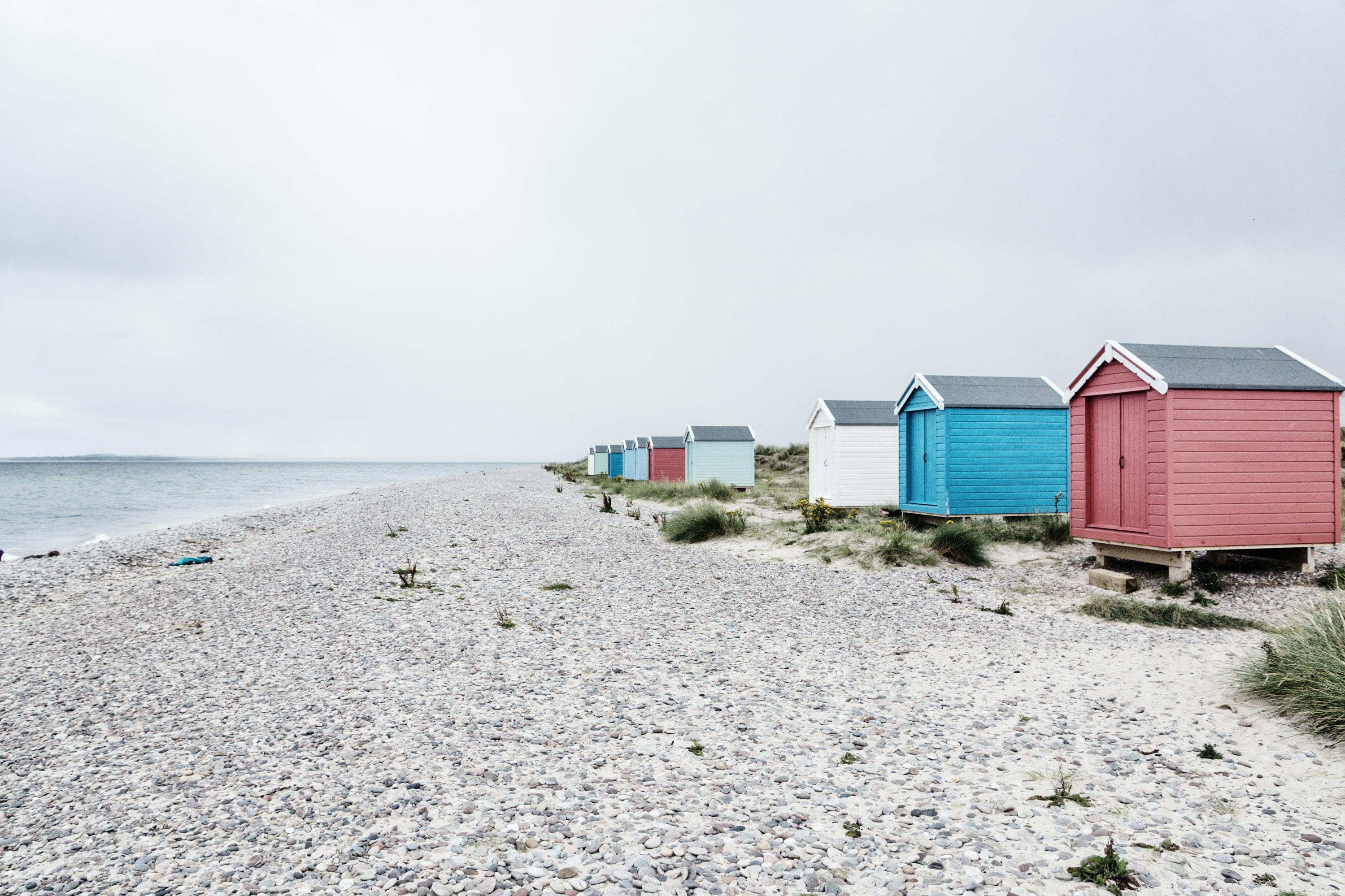 assorted-color sheds near seashore at daytime
