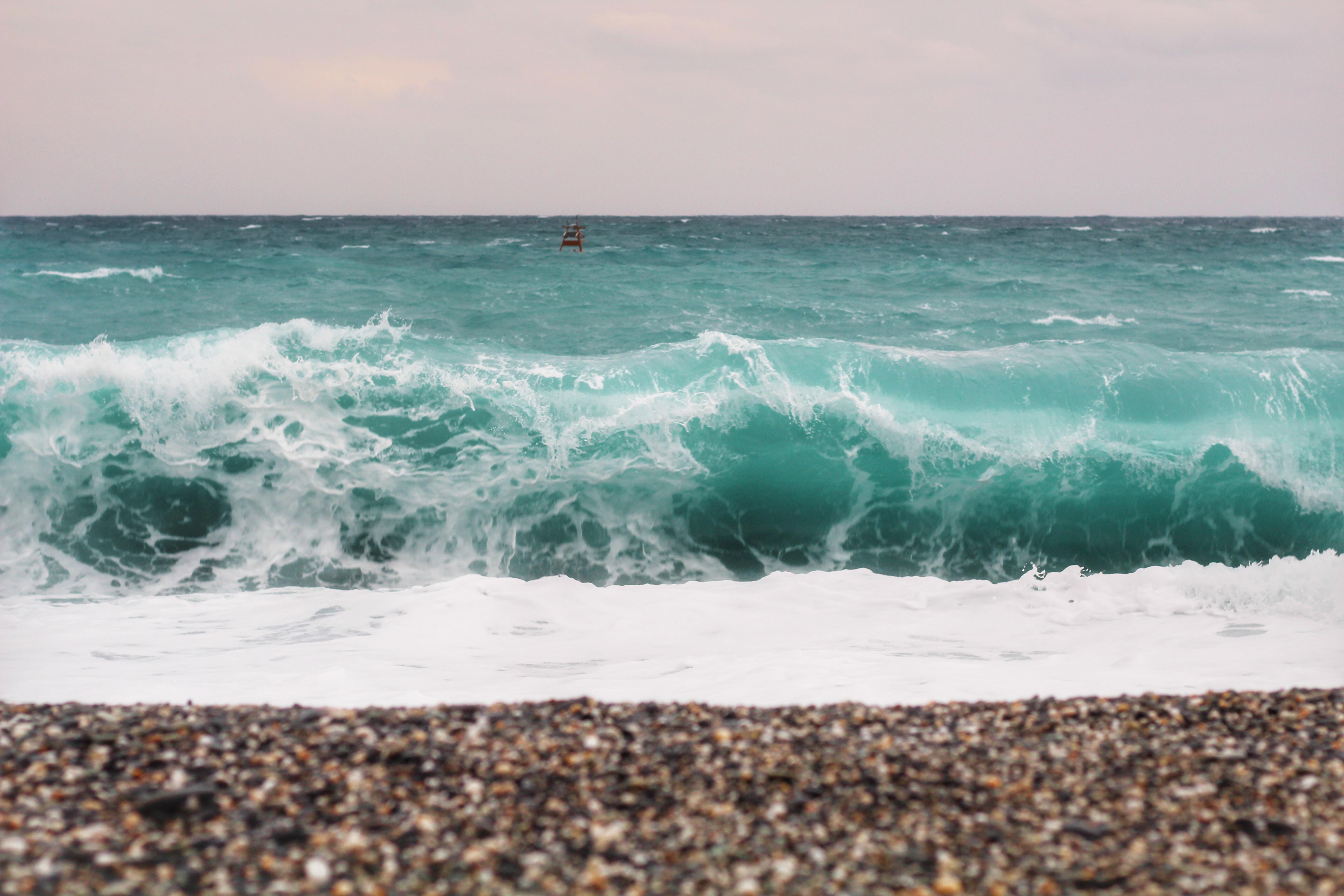 Wave crashing with foam on the pebble beach
