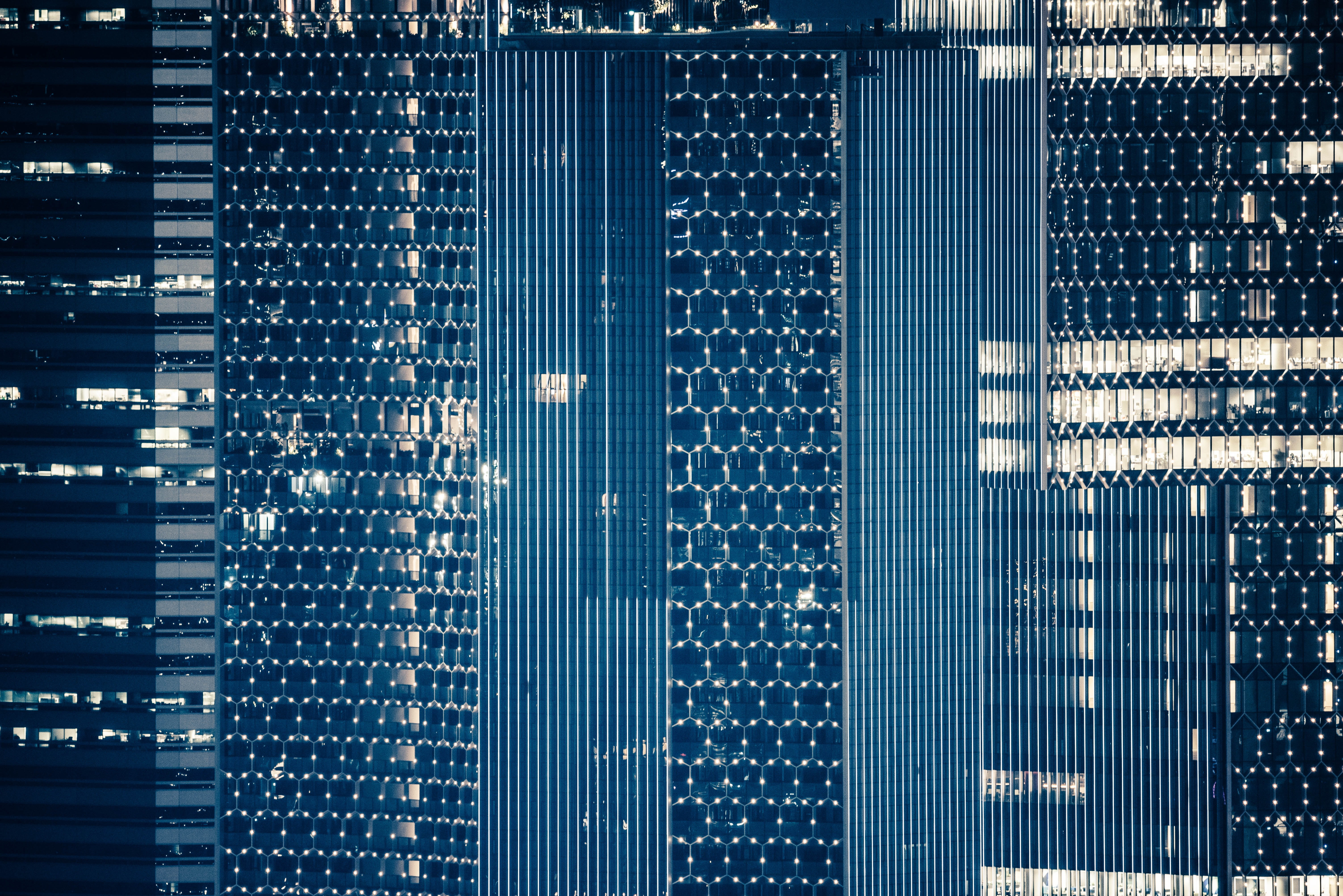 Macro of skyscraper's windows that are framed by light in honeycomb pattern