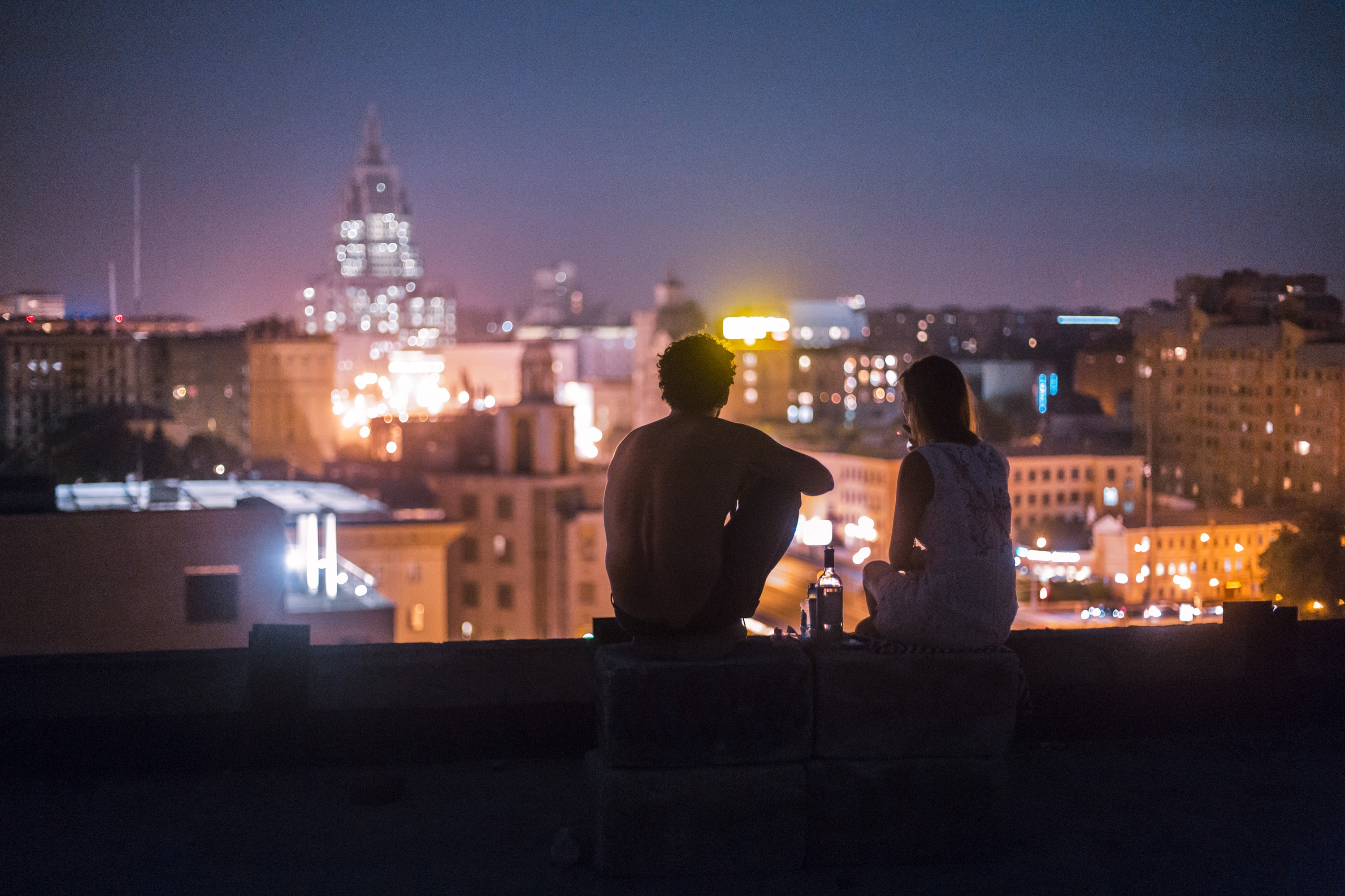 man and woman chilling on rooftop in front of high-rise buildings