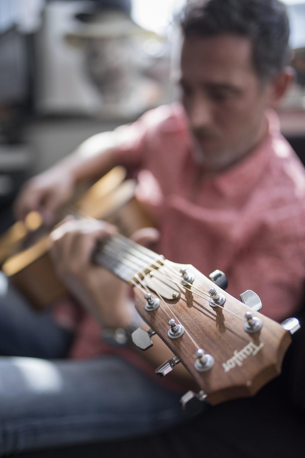 shallow focus photography of man playing guitar