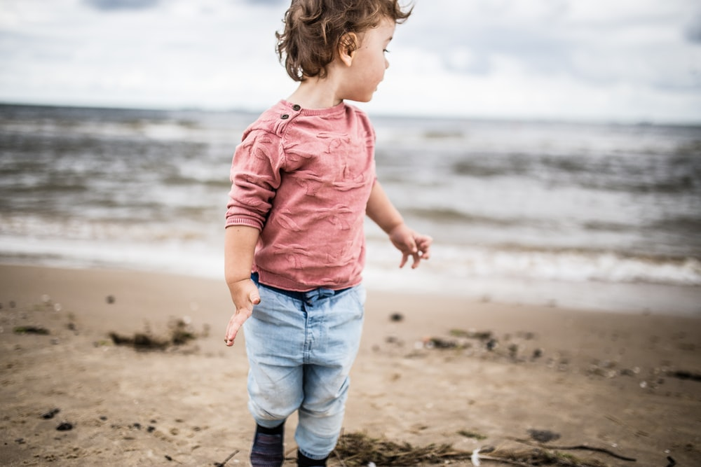 toddler boy standing on seashore