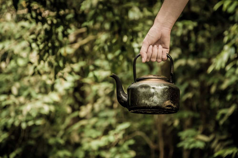 Hand holding a rustic vintage tea kettle outside