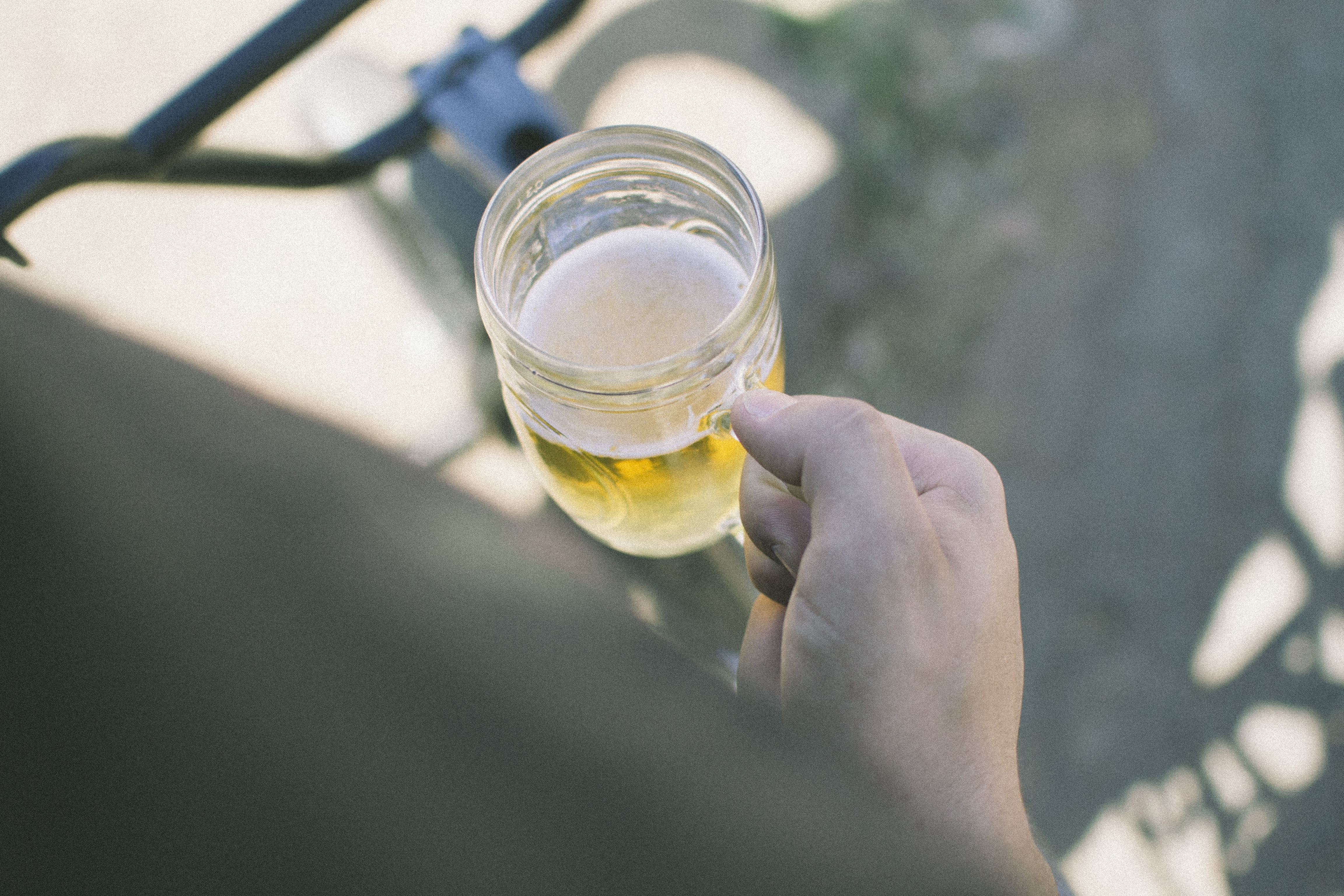A person holding a glass mug of beer