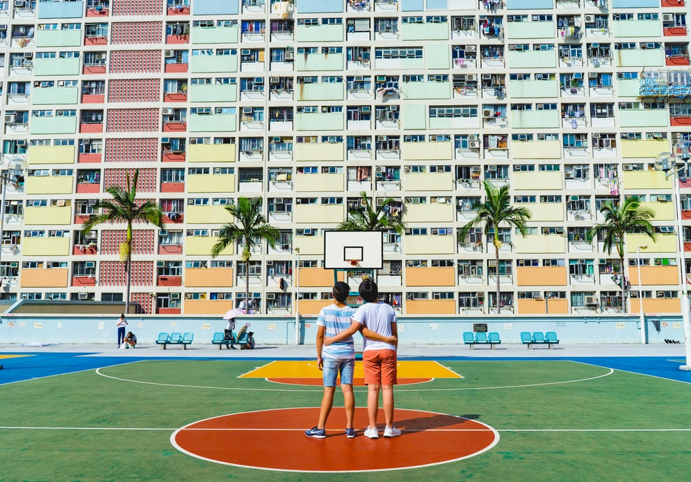 minimalist photography of two men standing on basketball court looking upwards