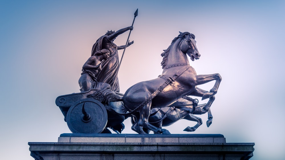 two men riding carriage statue