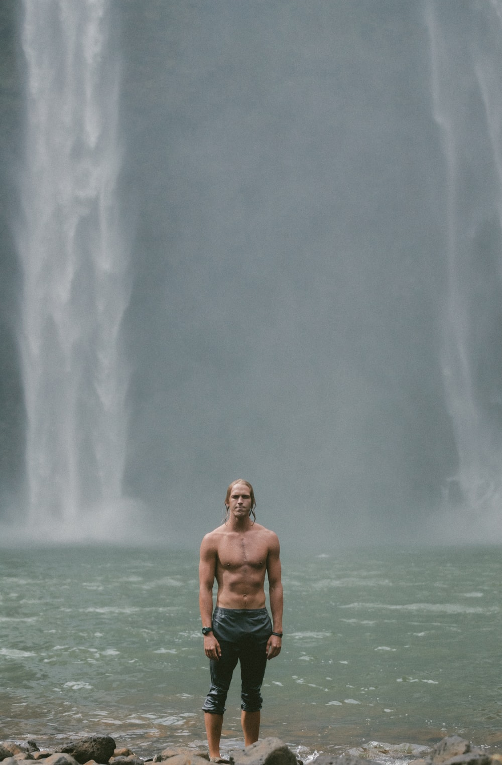 topless man standing in front waterfalls