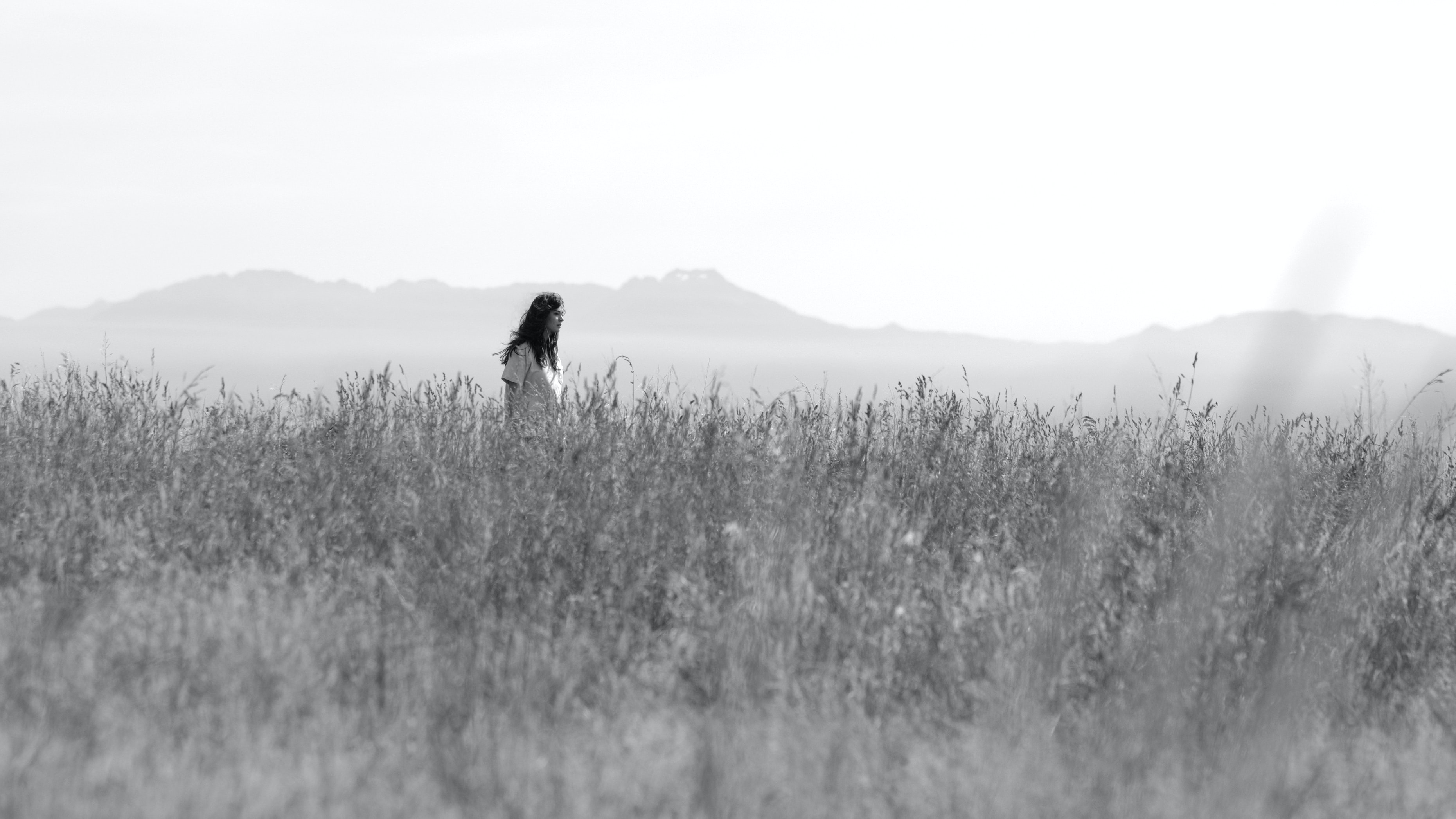 grayscale photography of woman on fields