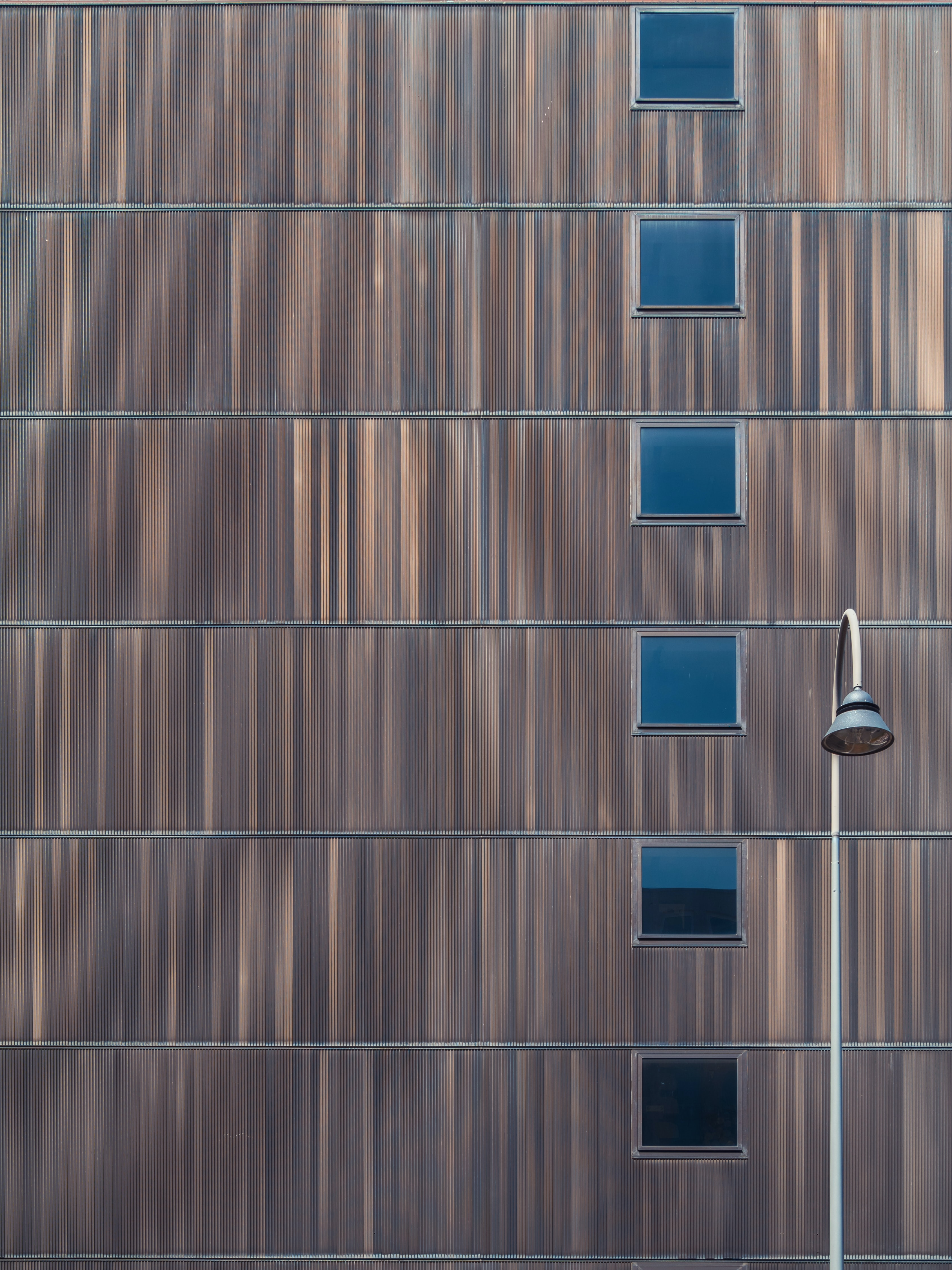 minimalist photography of arch post lamp near high-rise building