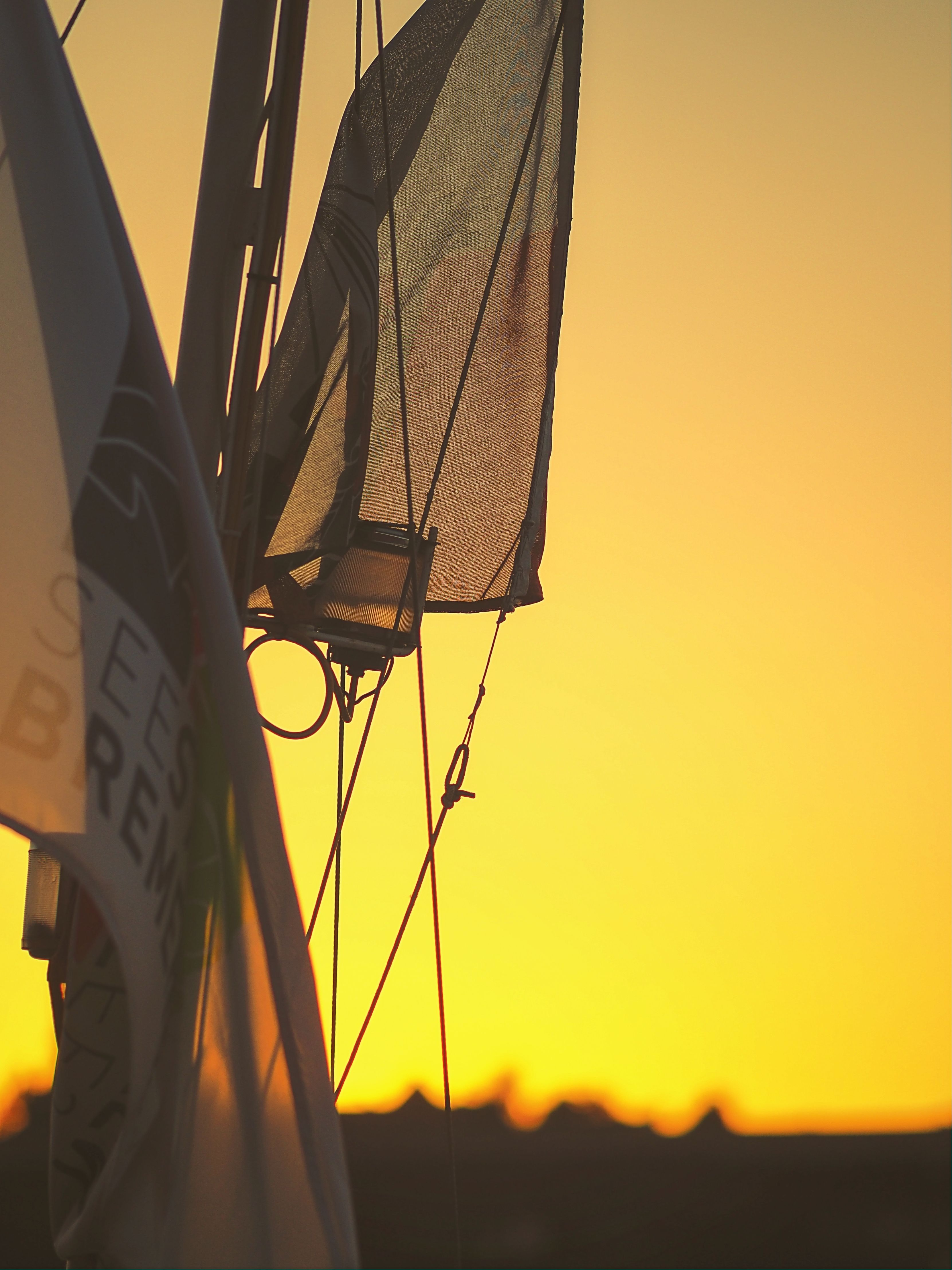gray and black sailboat during sunset