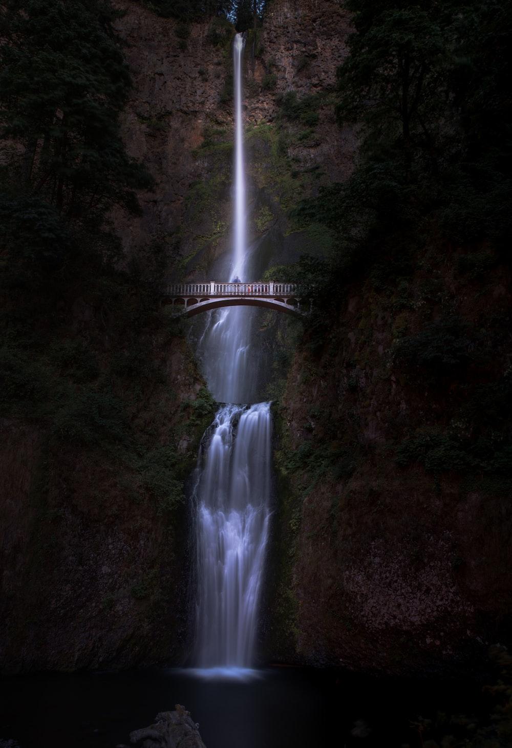bridge near waterfalls at daytime