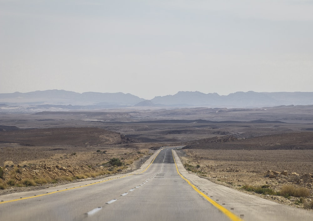 gray asphalt road towards open valley t
