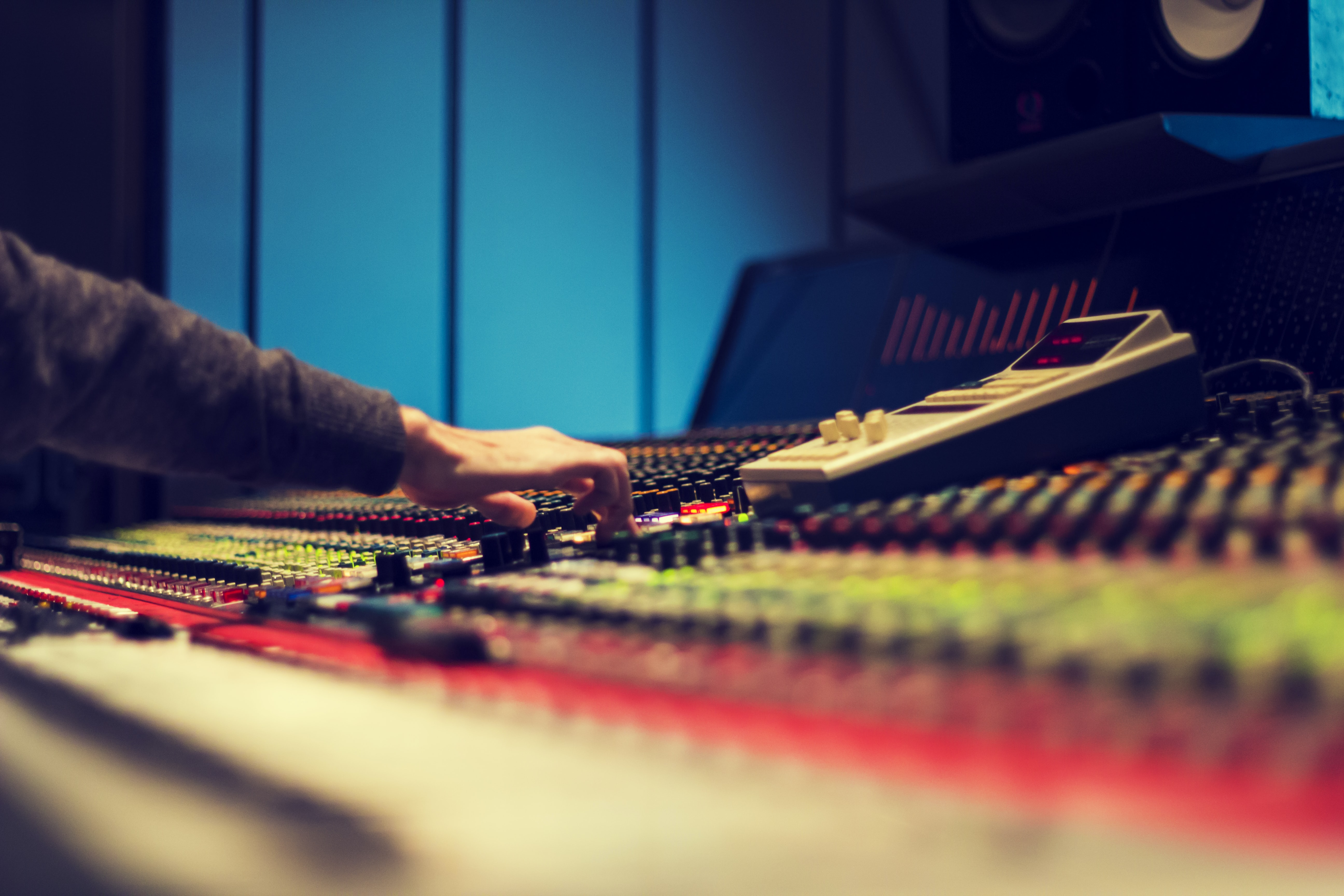 A close-up of the hand of a sound engineer making adjustments on the soundboard.