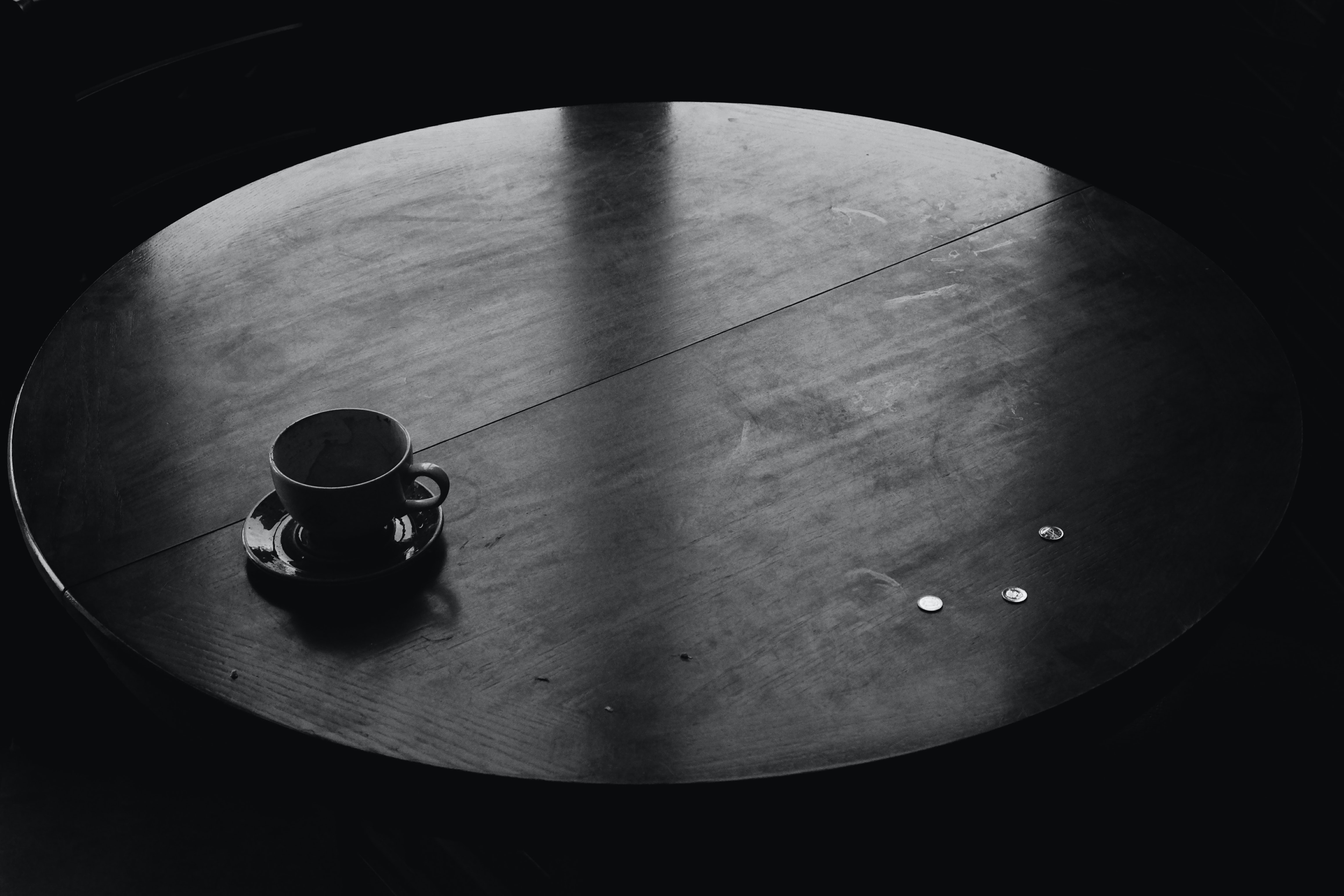 White mug on black plate on a black wooden table with three quarters on it in a dark room
