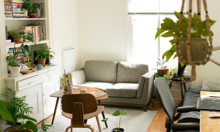 gray fabric loveseat near brown wooden table