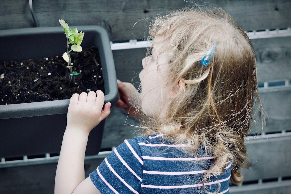 girl holding onto a plastic pot