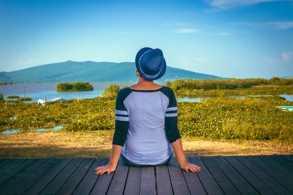woman sitting on brown wooden dock taken at daytime