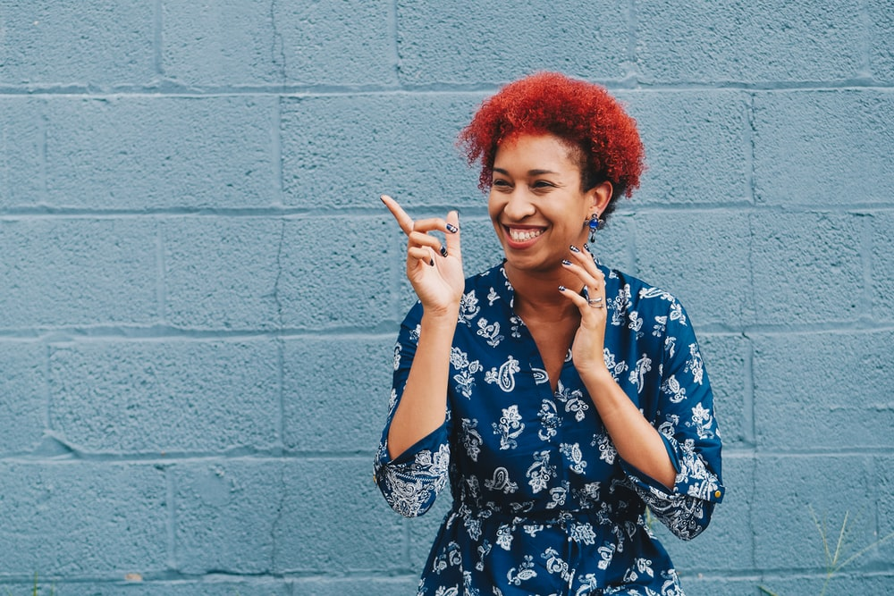 woman smiling while pointing on her right side