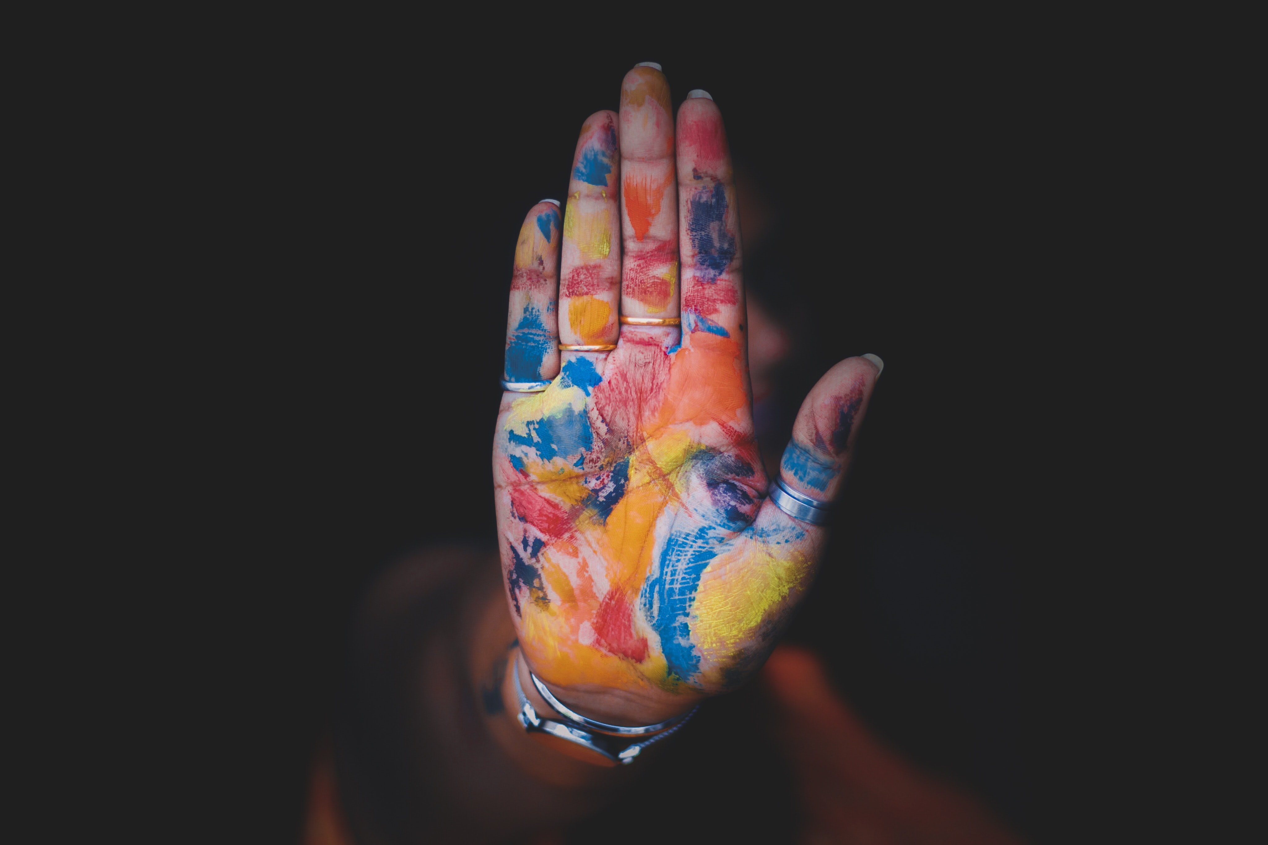 A person with paint smudged on her hand and rings around four of her fingers