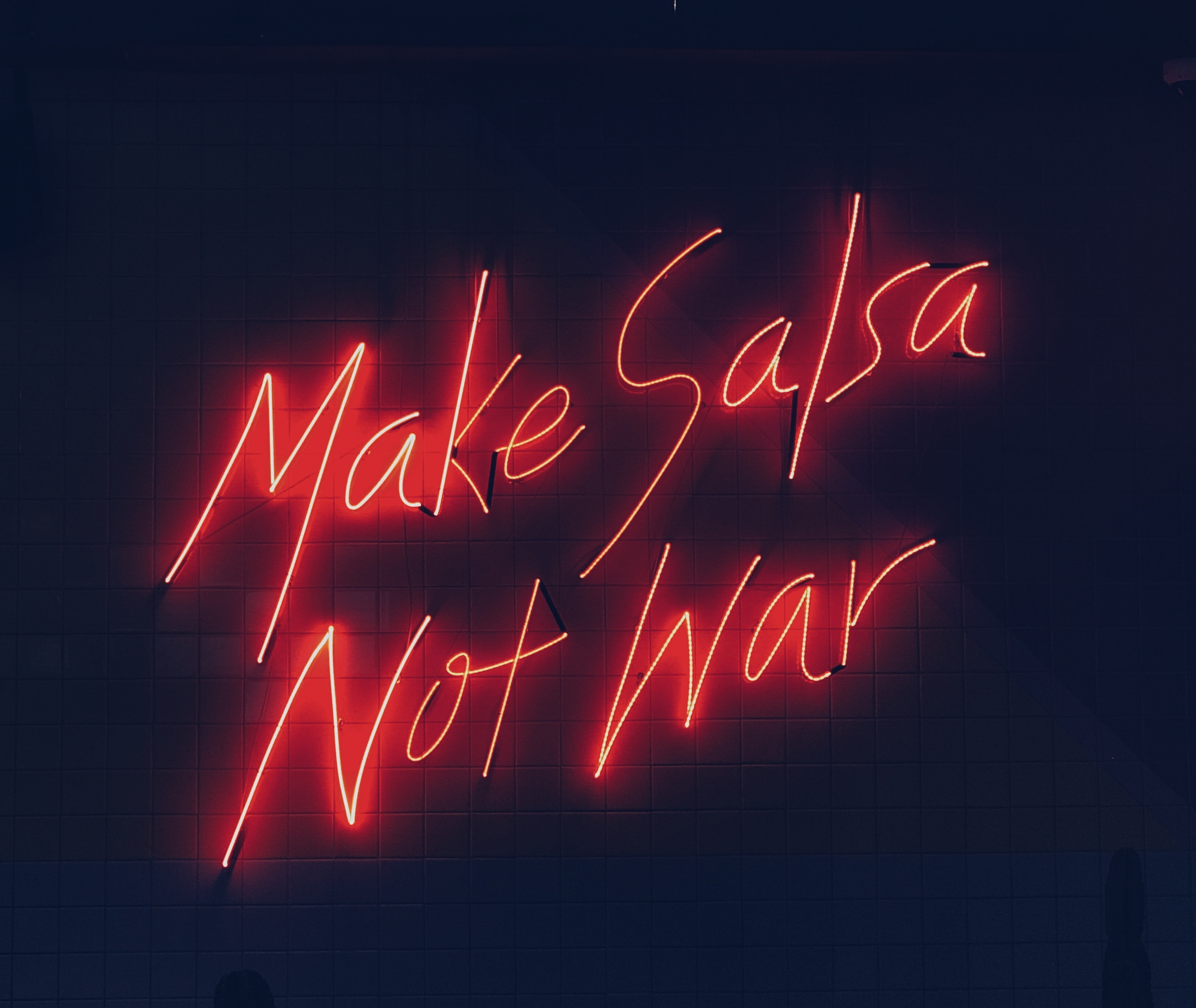 A neon sign that says make salsa not war