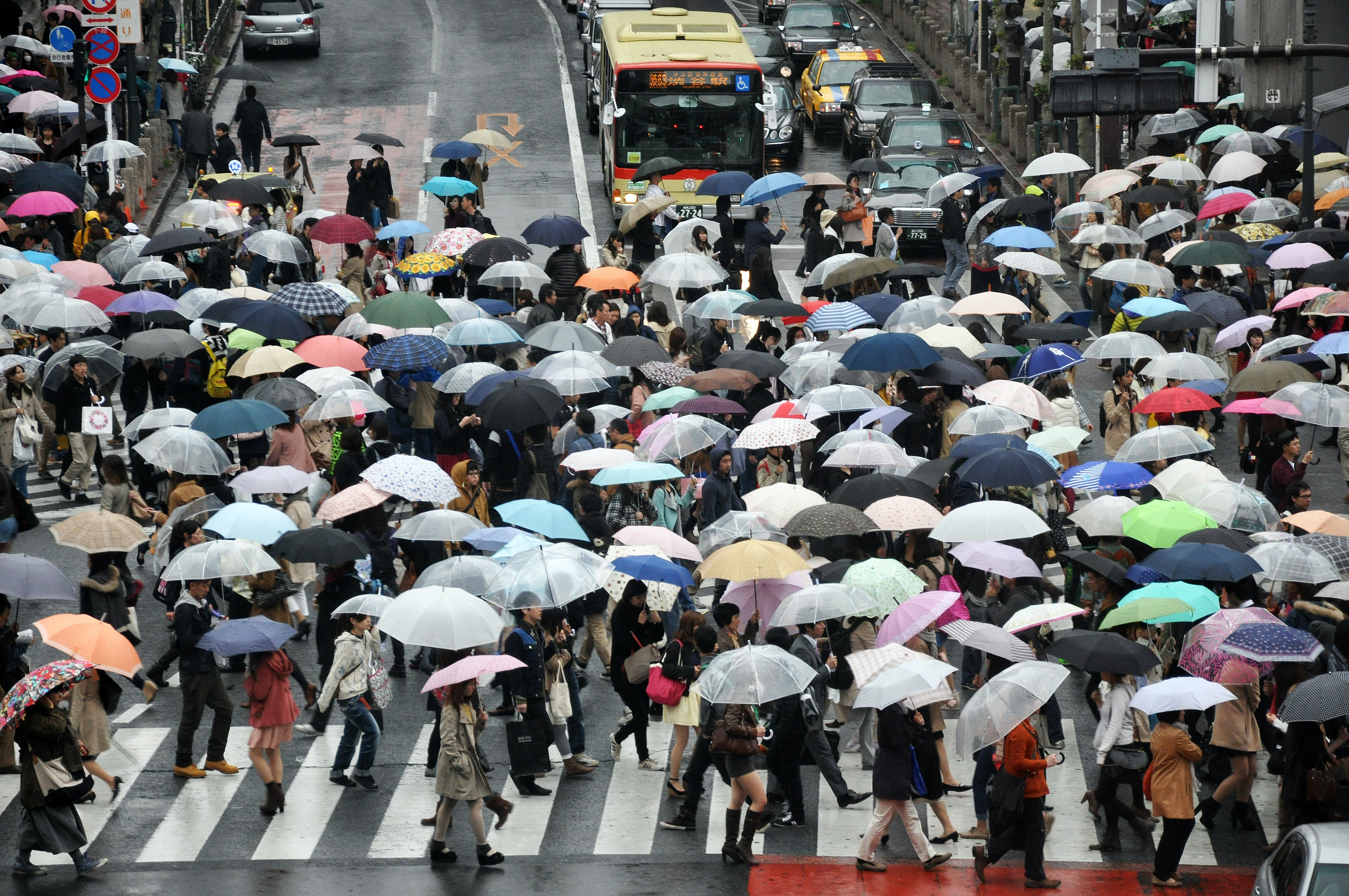 A crowded crosswalk in Tokyo on a rainy day