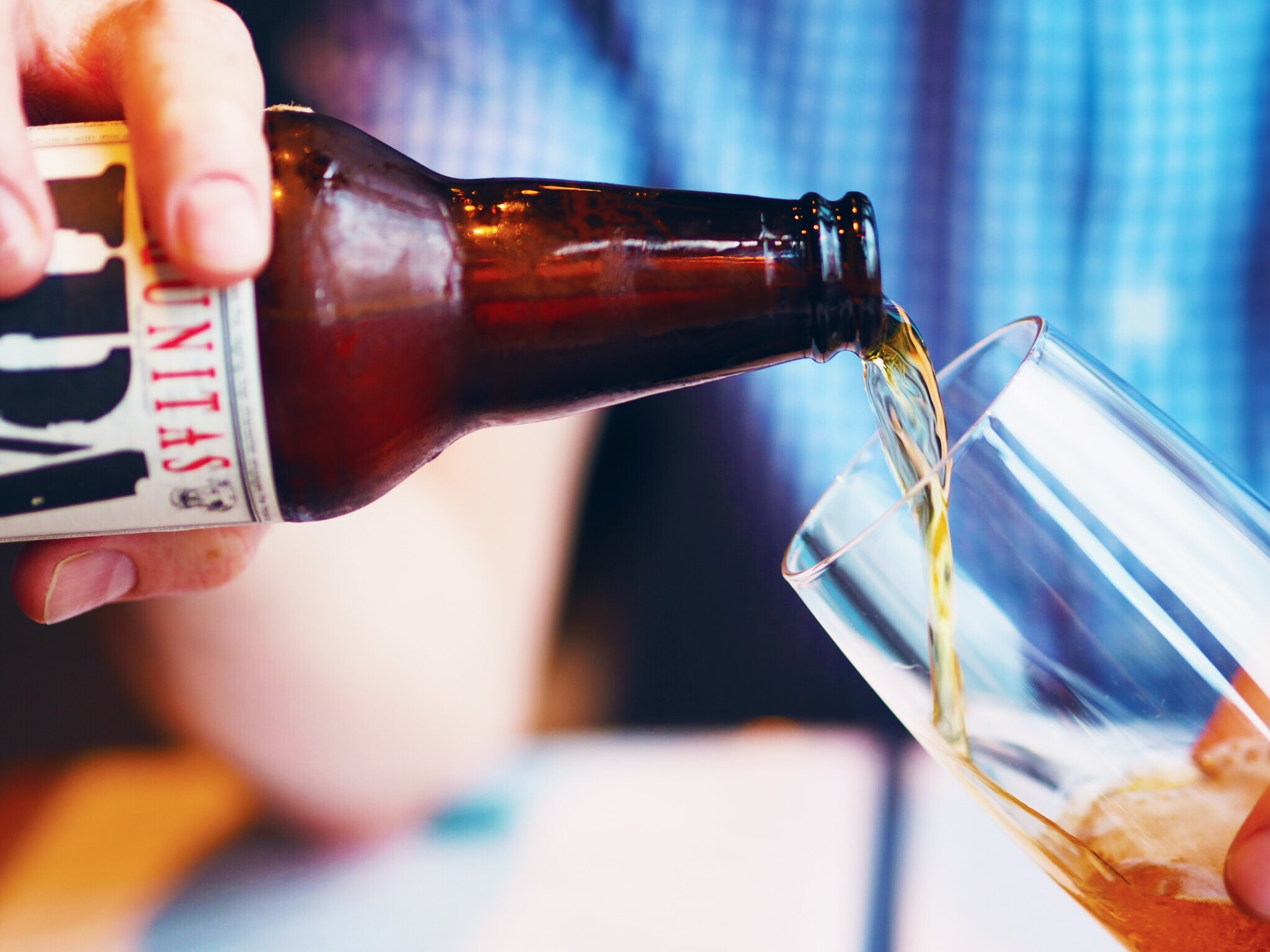 person holding amber glass bottle pouring liquid on drinking cup