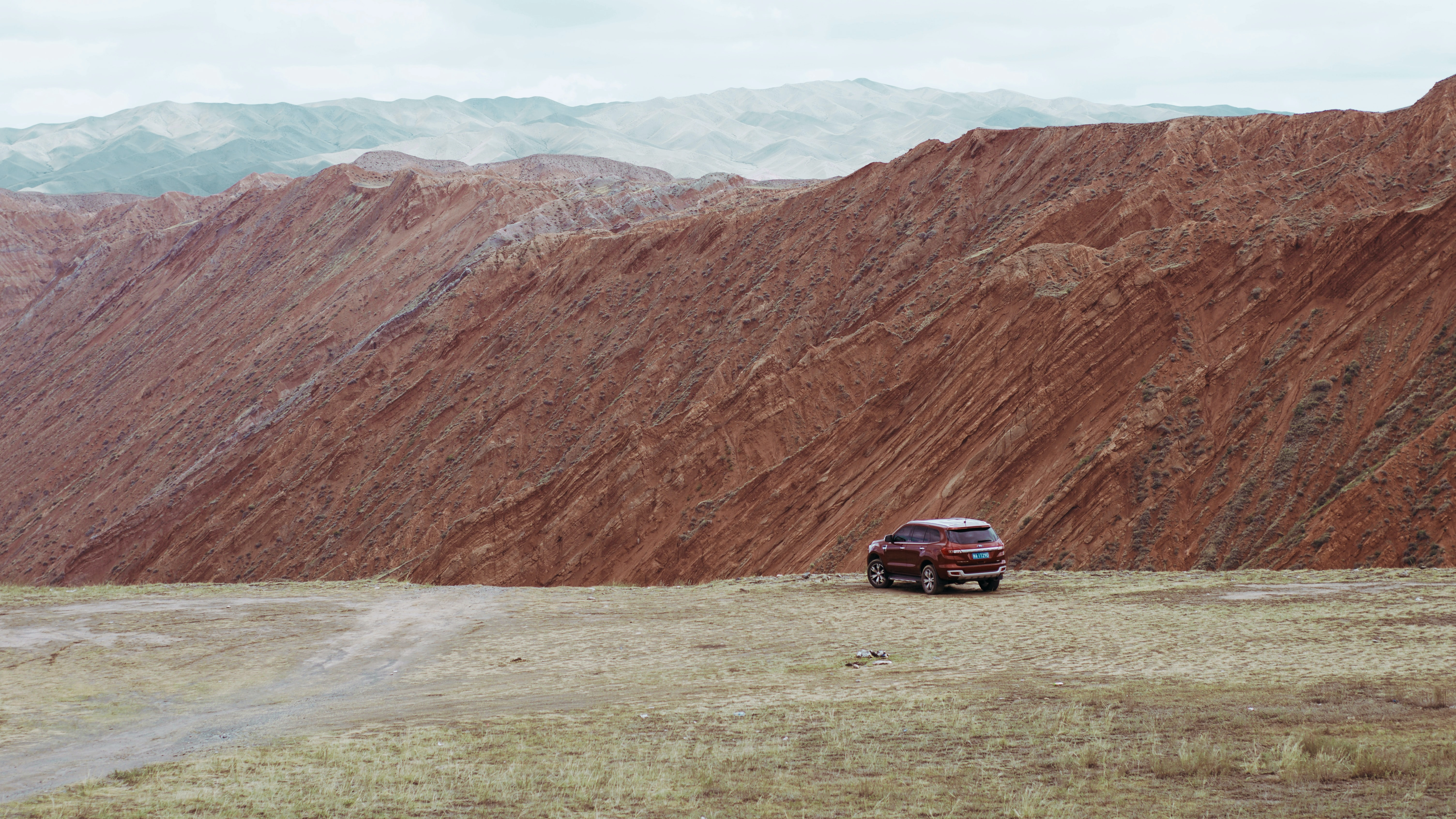 red SUV near the edge of a mountain during day