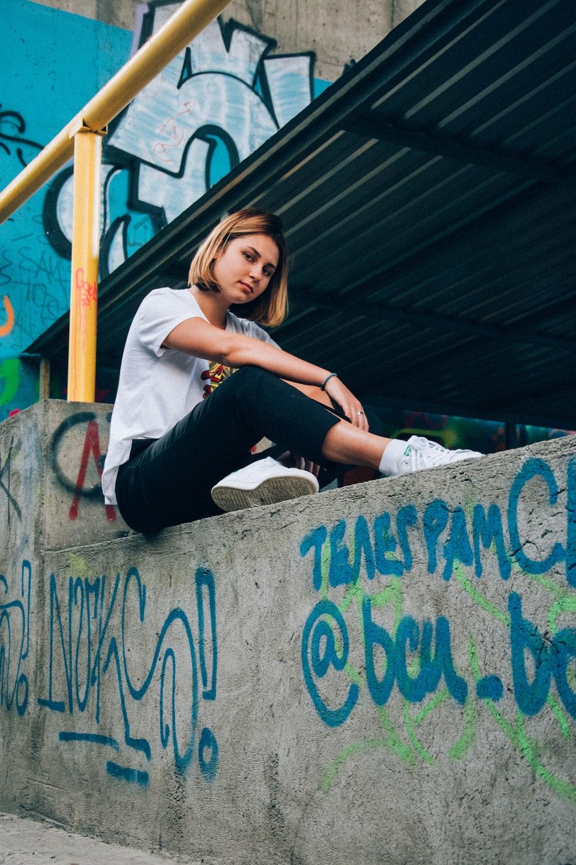 woman sitting on gray concrete pavement