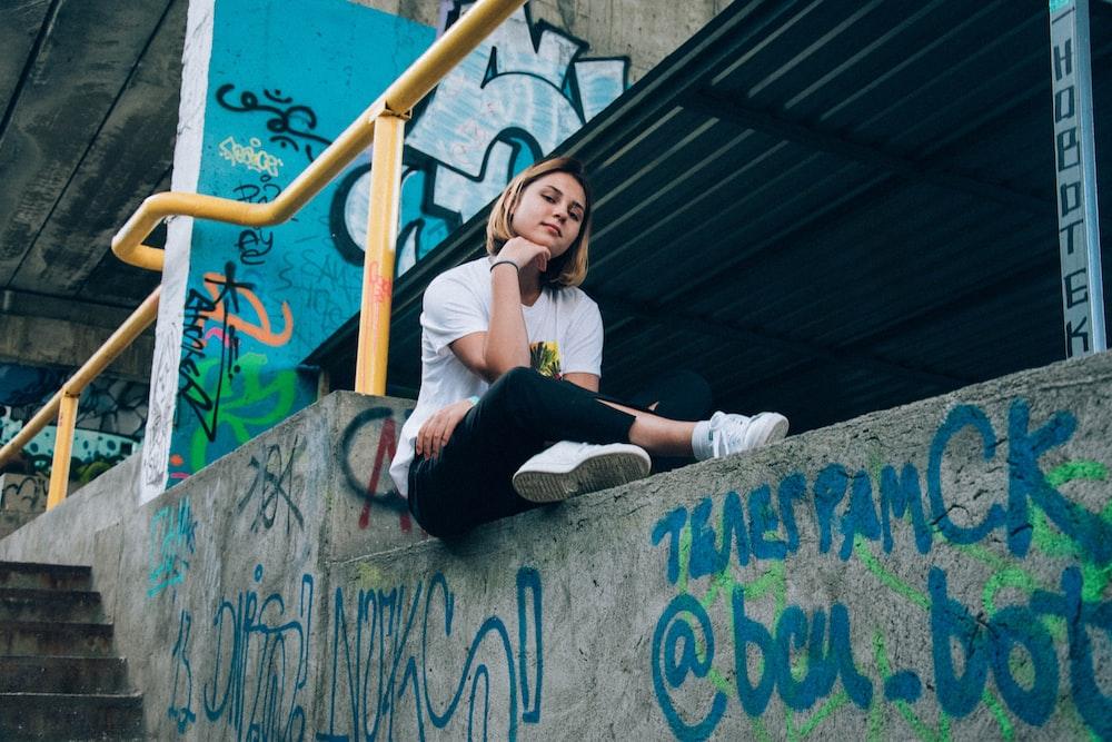 woman wearing white shirt and black pants sitting on concrete rail