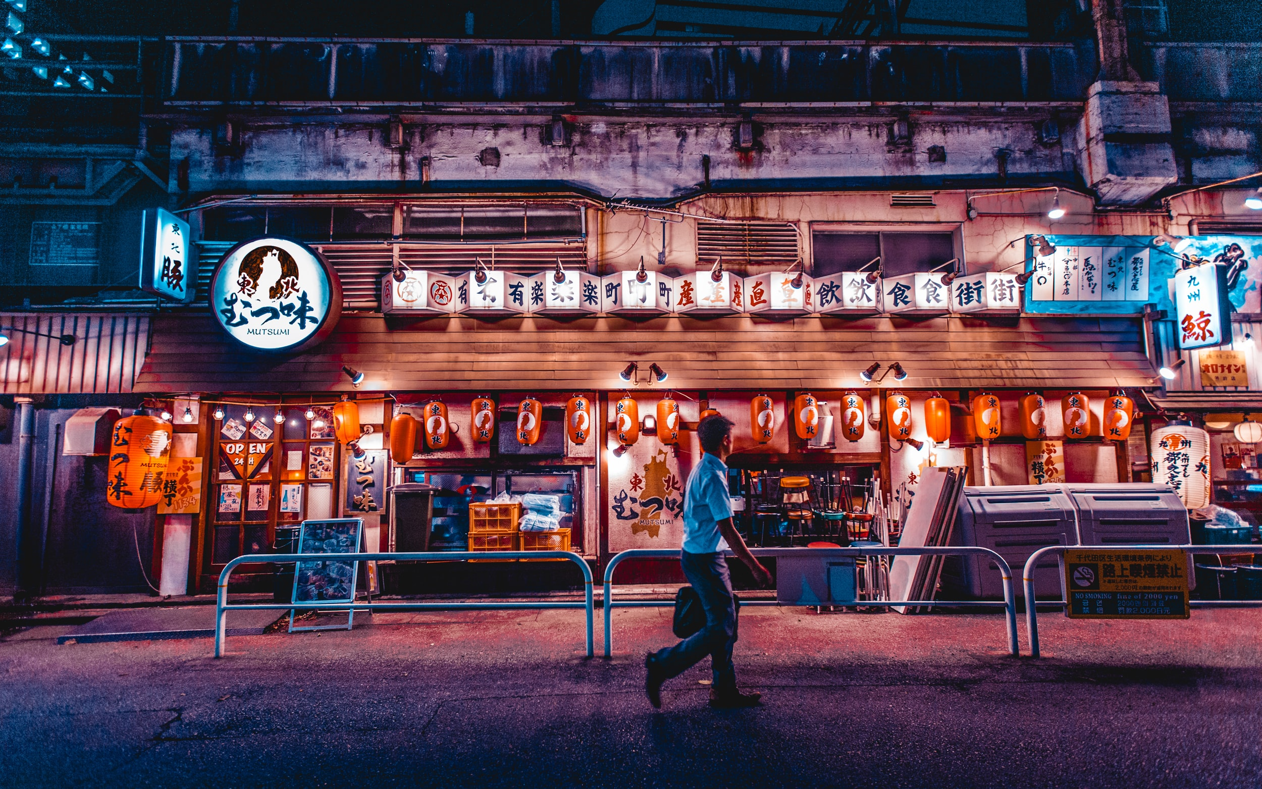 A lone man walking past a restaurant storefront in Tokyo at night