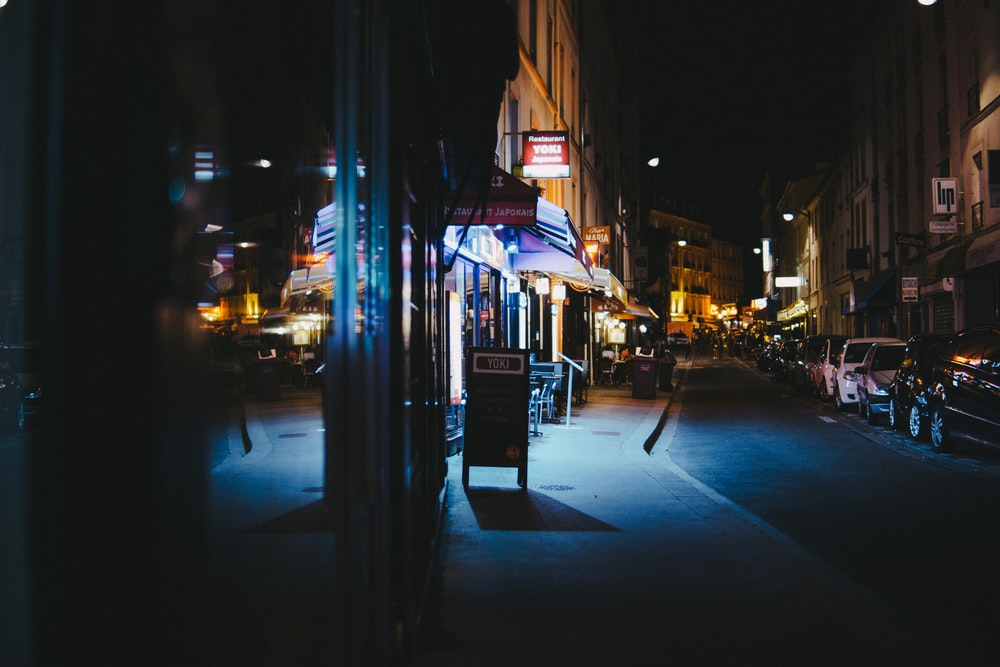 cars parked in front of stores during nighttime