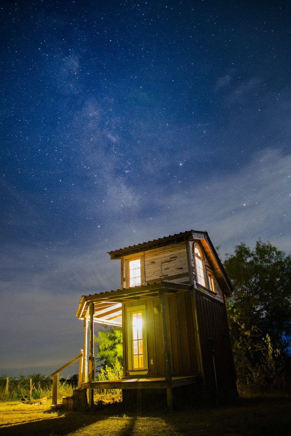 brown wooden house beside green leaf at night time