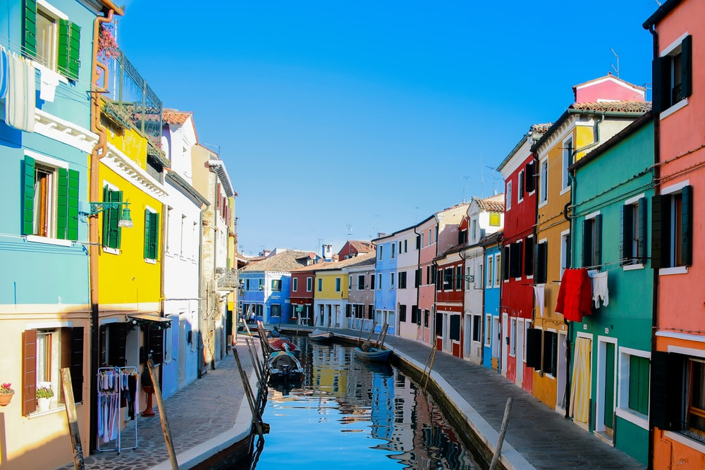 water canal between assorted-color buildings at daytime