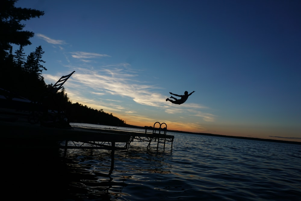 silhouette of person diving on water