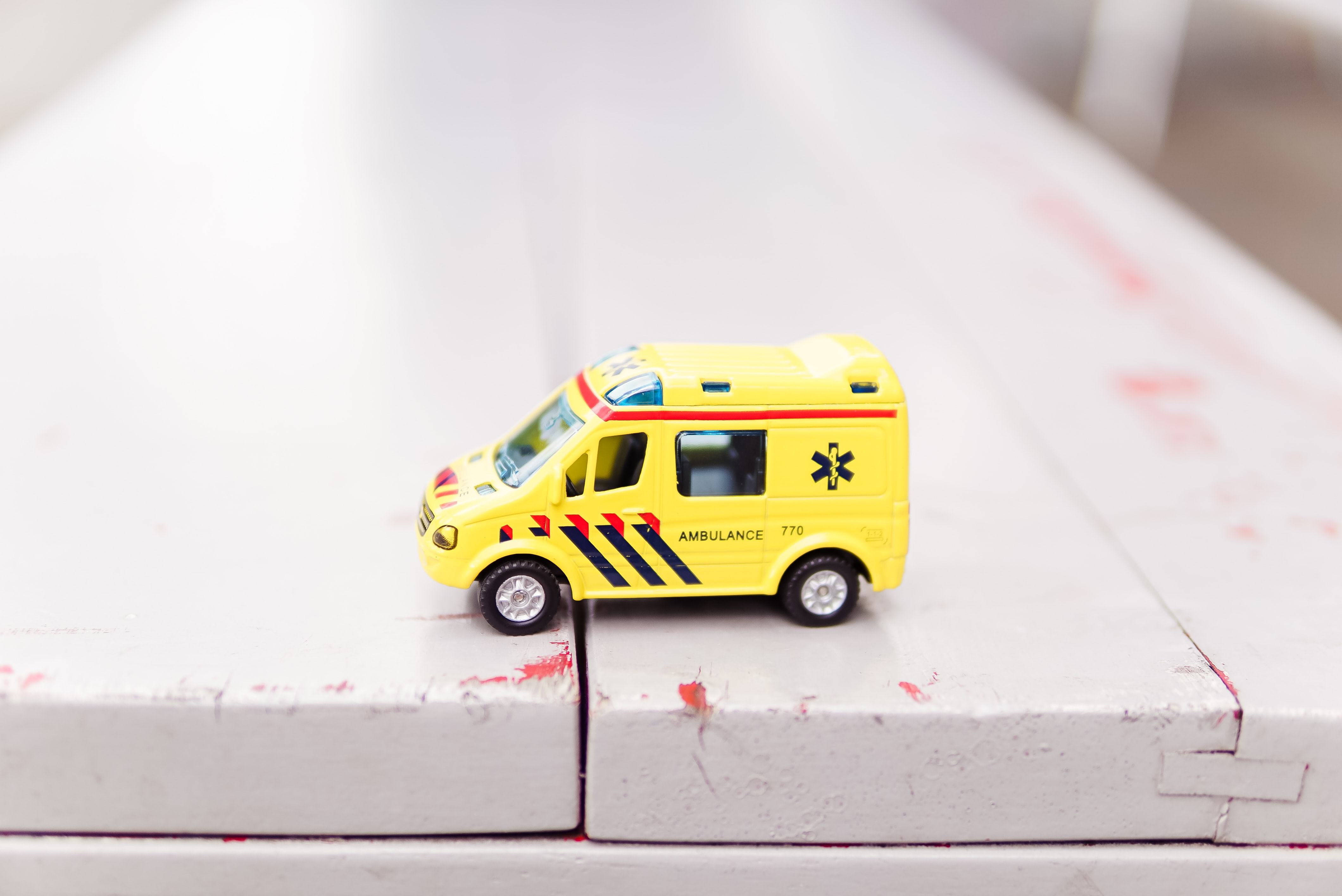 A yellow toy ambulance on a painted wood surface.