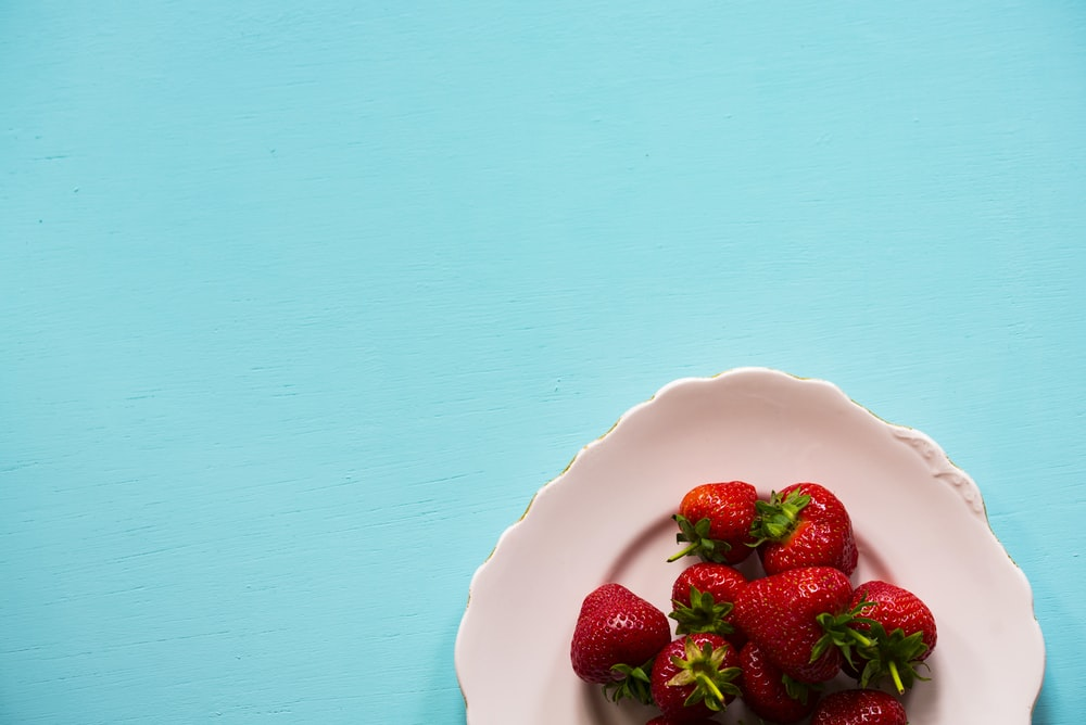 flat lay photography of bunch of strawberries on white plate