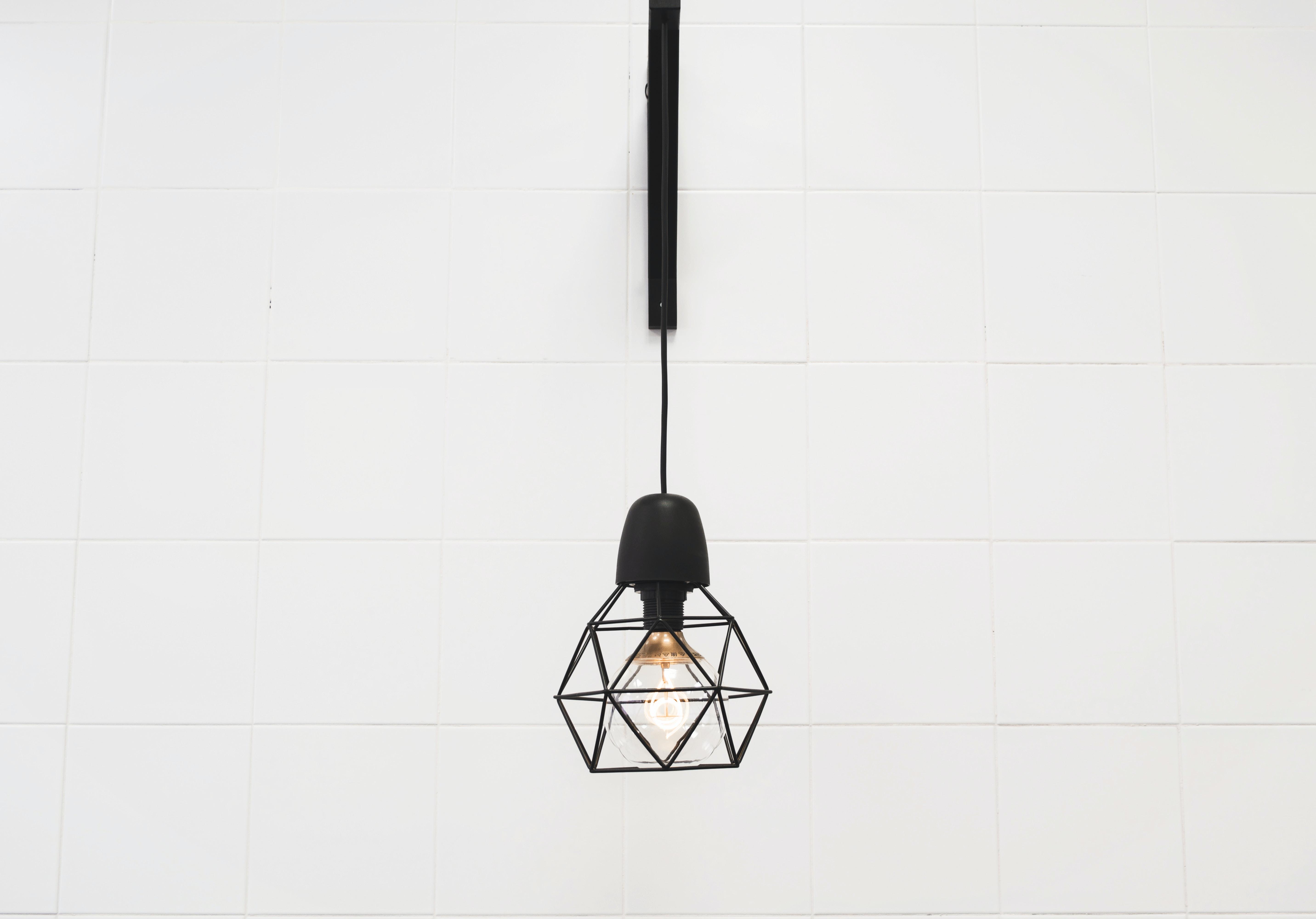 Single geometric lantern with light bulb hanging on a white wall