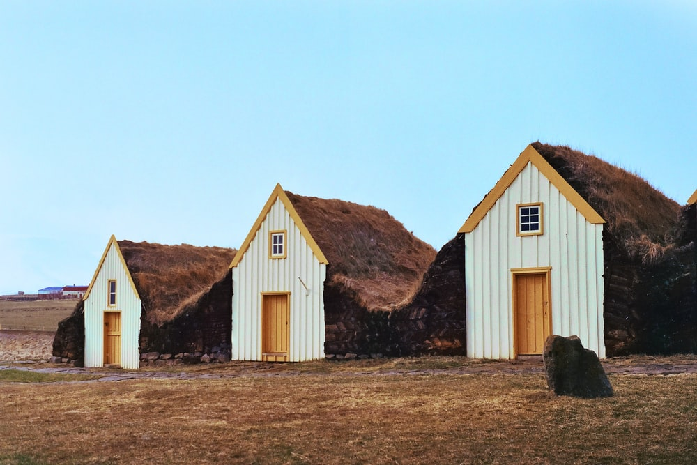 three white-and-brown houses