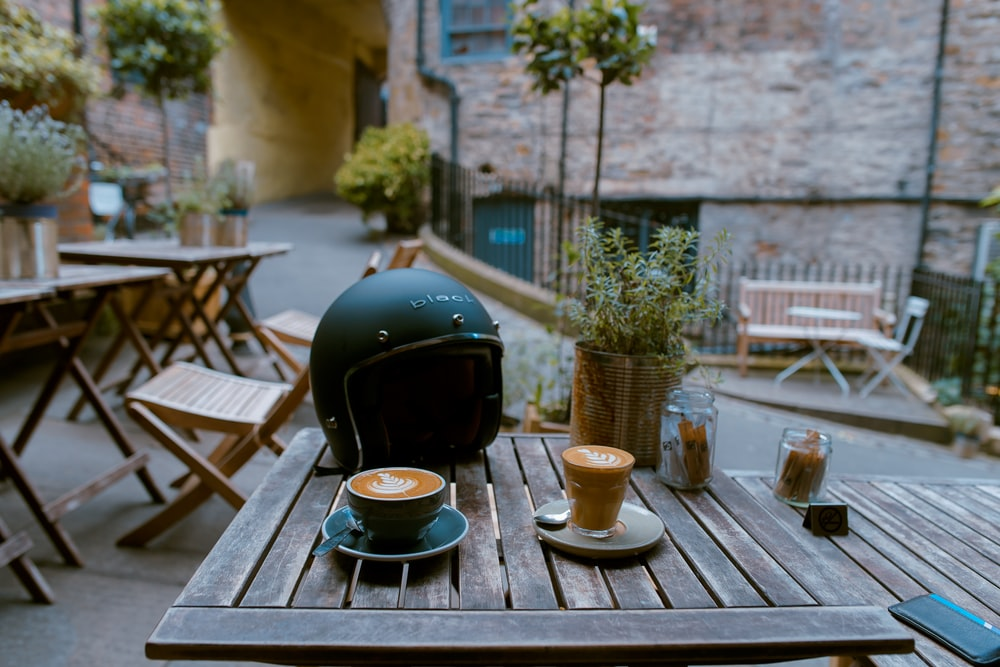 espresso filled cups near the motorcycle helme