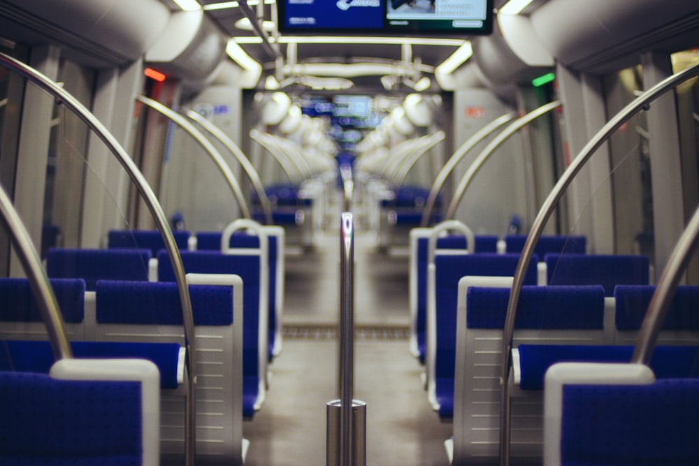 An empty train with blue seats and circular hand rails and monitors