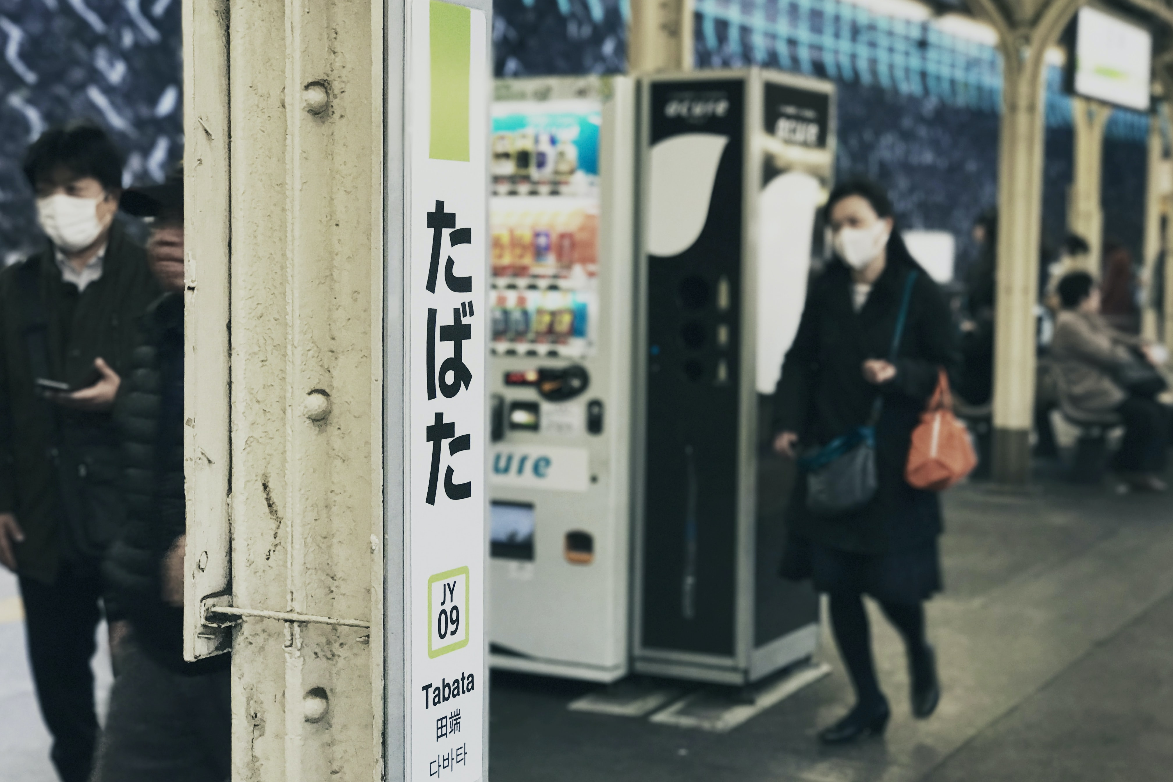 Tabata Station sign on a train station pillar beside a vending machine and Japanese public wearing mouth masks