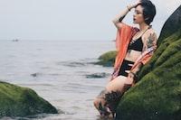 woman wearing black bikini leaning green grass near sea