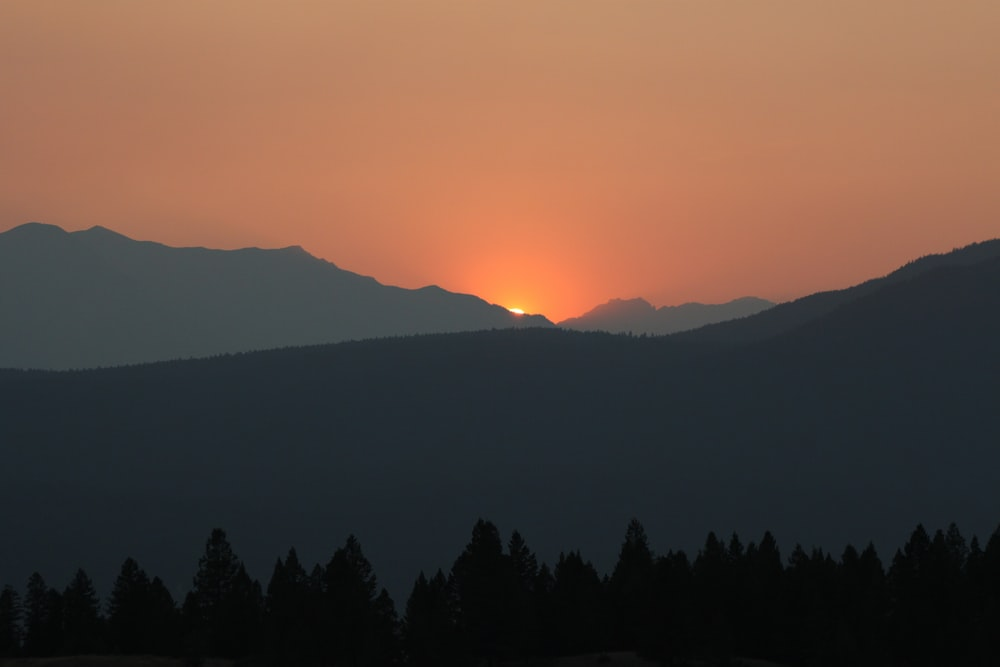 silhouette photography of mountain during sunset