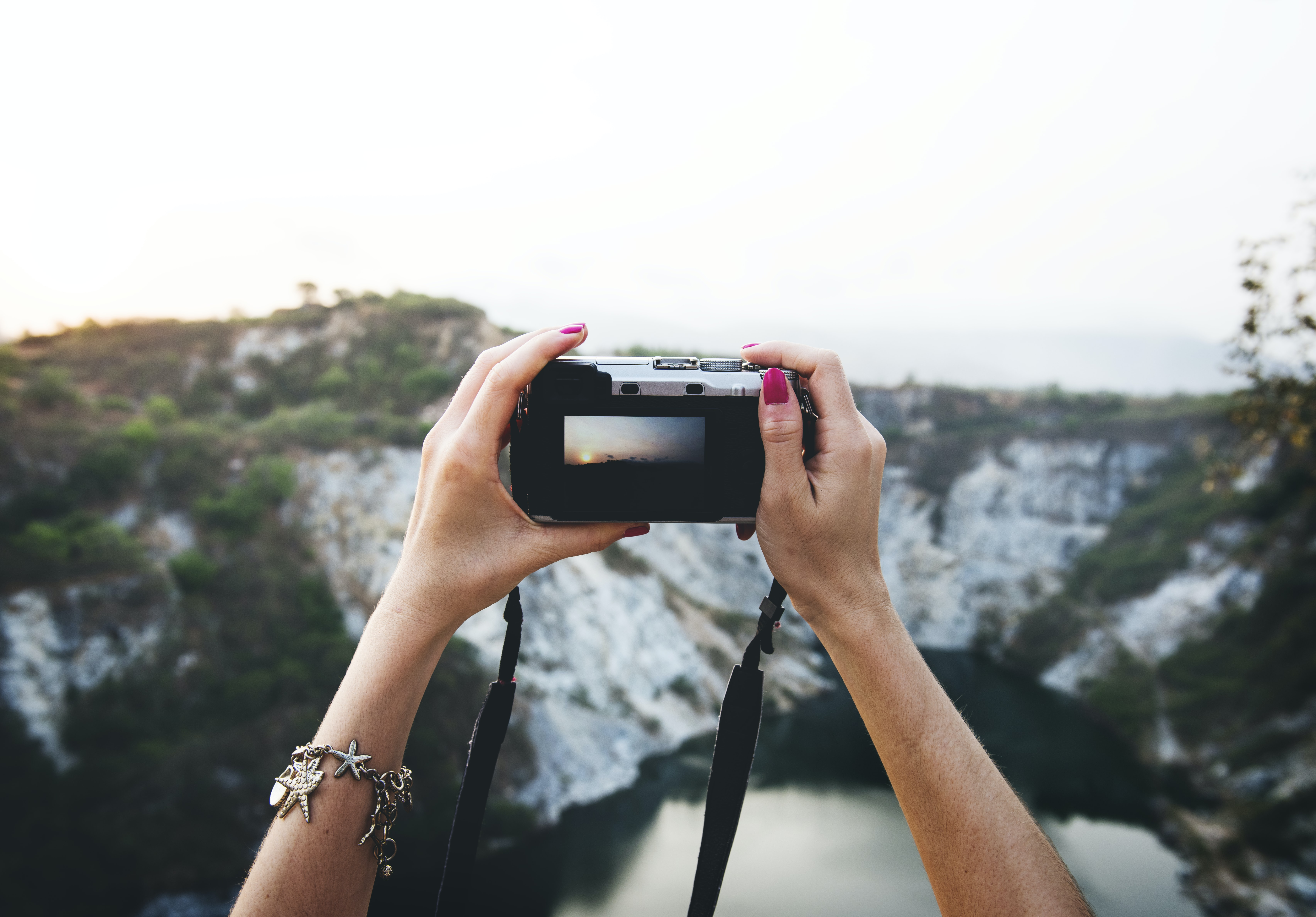 woman holding camera upwards facing cliff and lake during daytime
