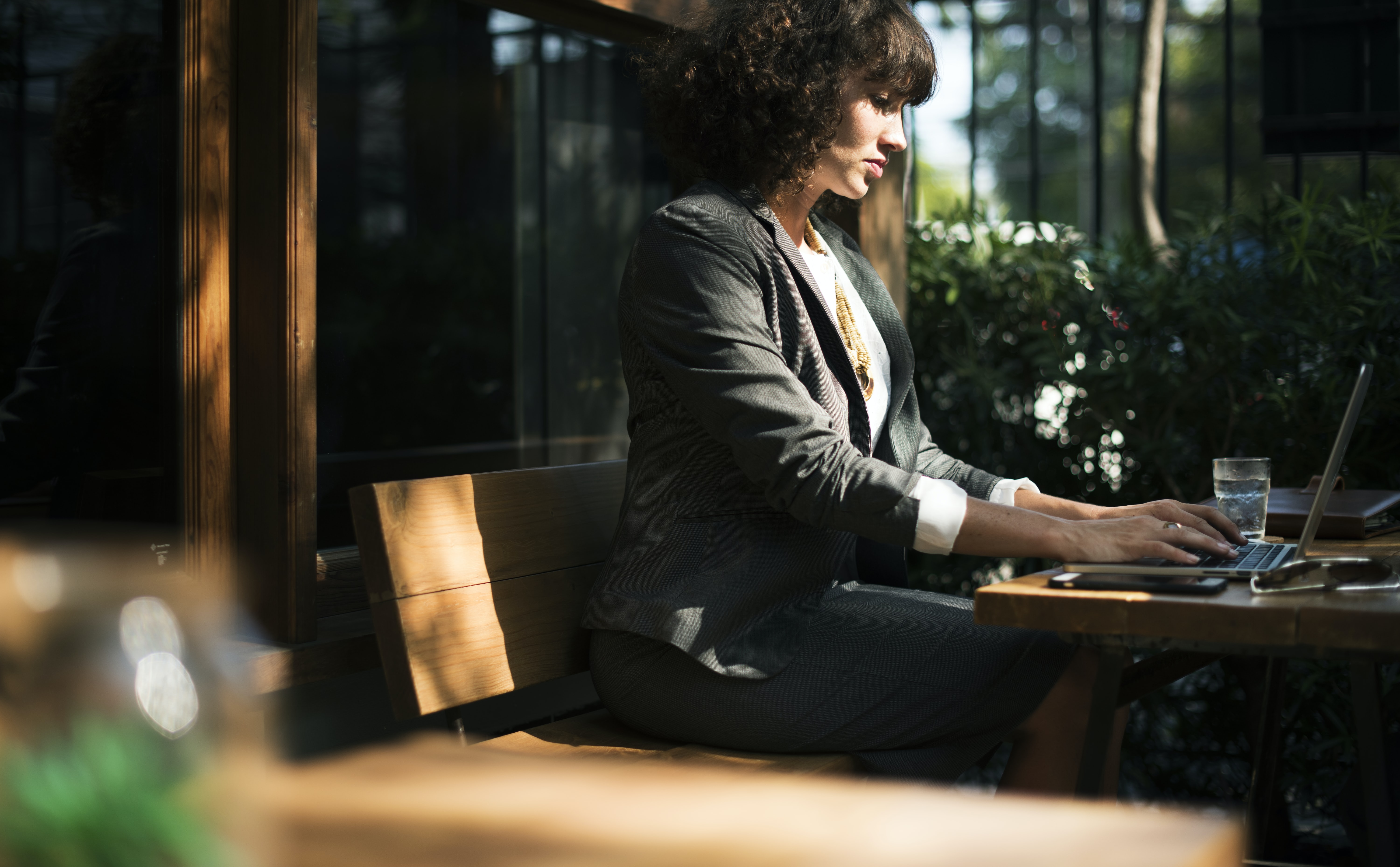 A businesswoman sitting at an outside table and typing on a table