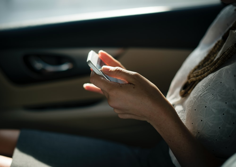 Woman sitting in car in the sunlight with a smartphone in her hands