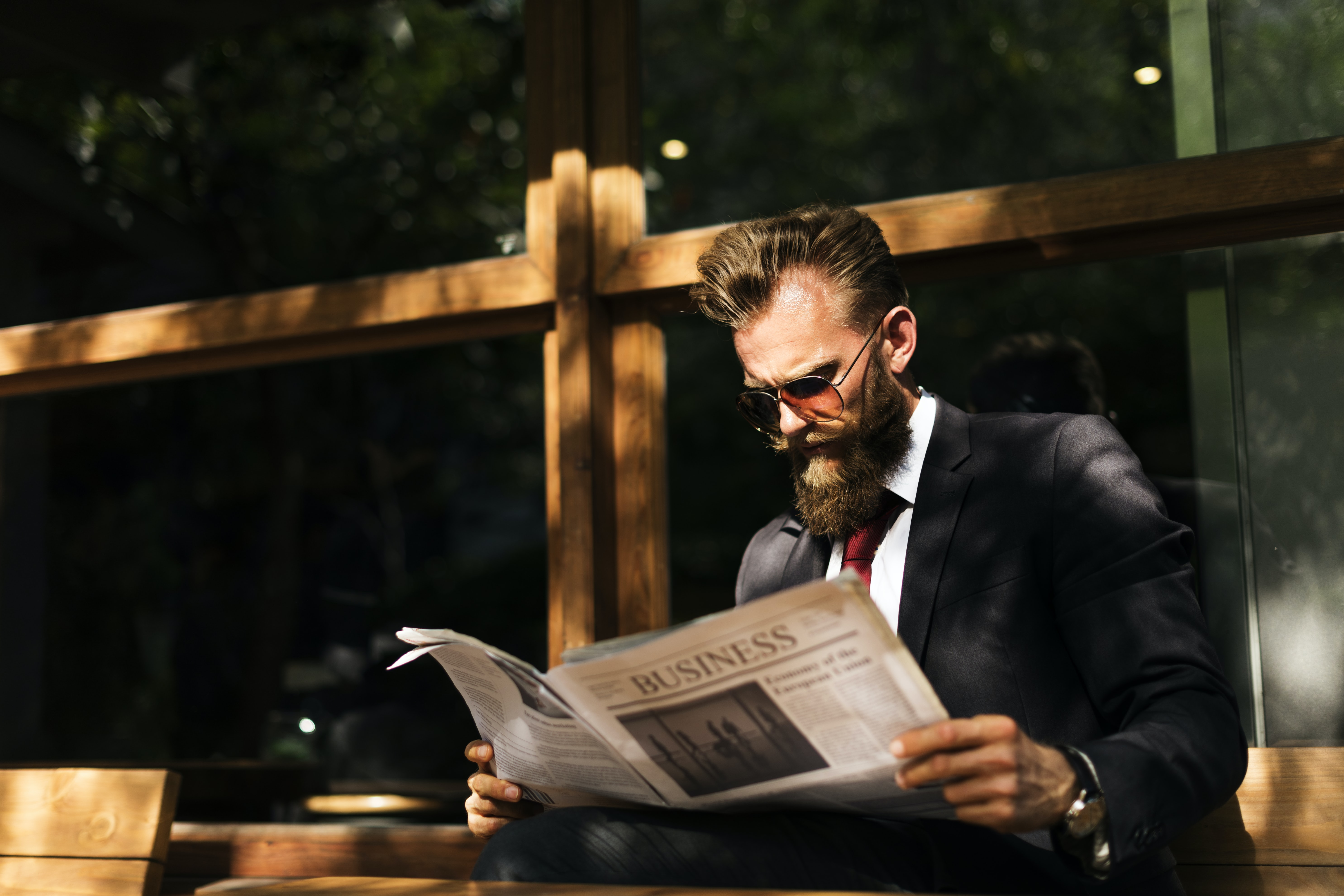An elegant bearded man in a suit reading a newspaper on a wooden bench