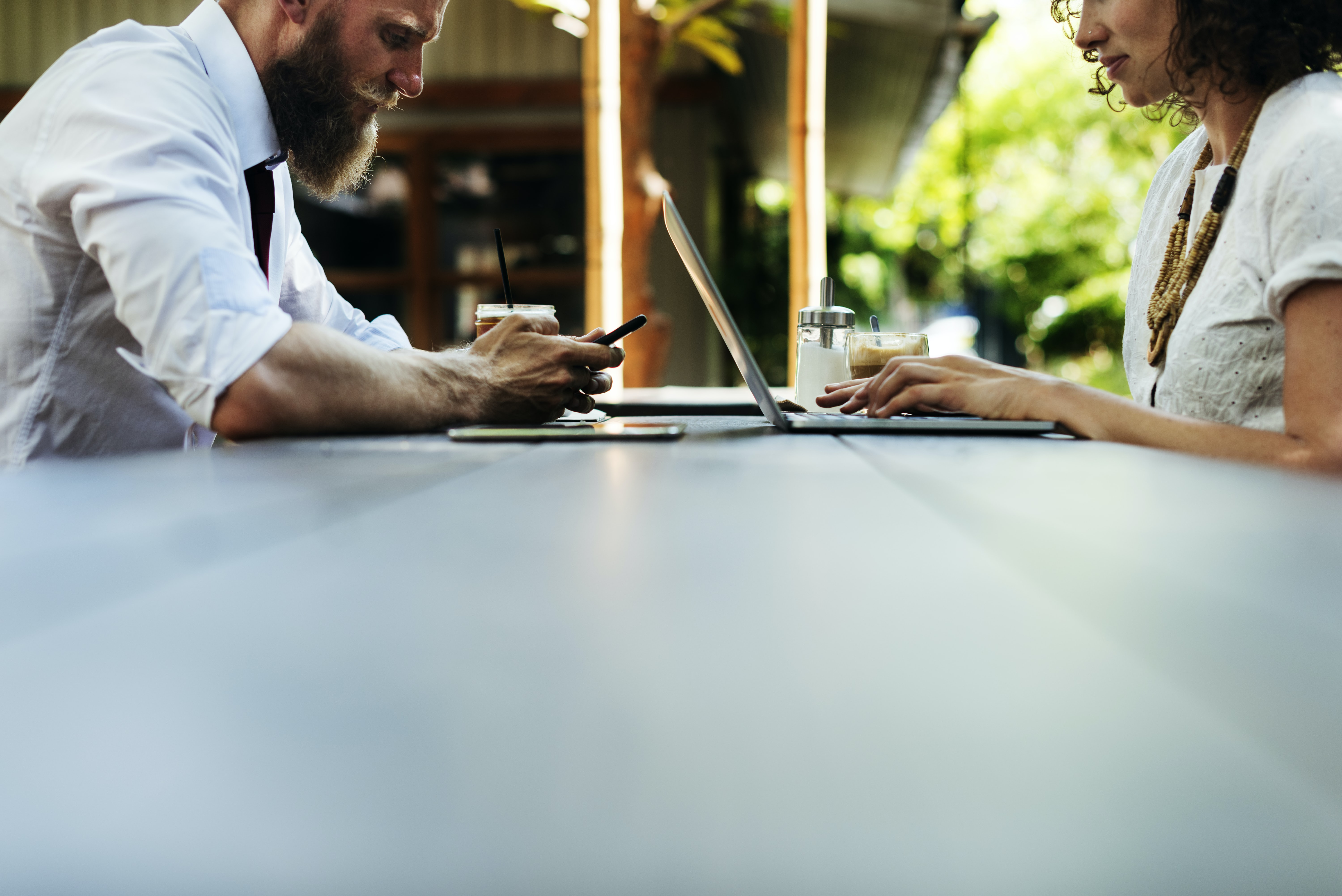 low angle photography of man and woman working in front of table