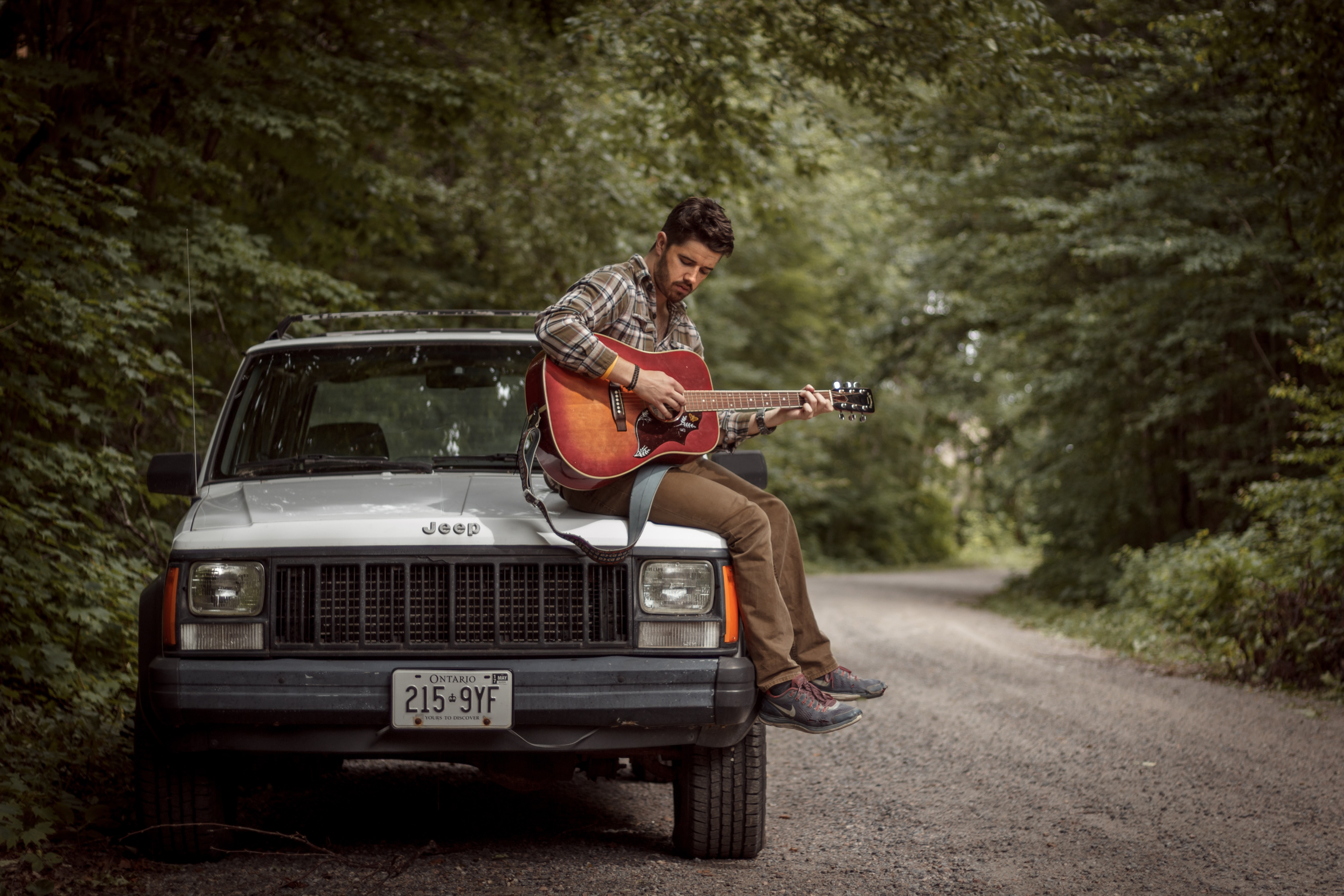 Musician sitting atop his jeep playing guitar on a country road