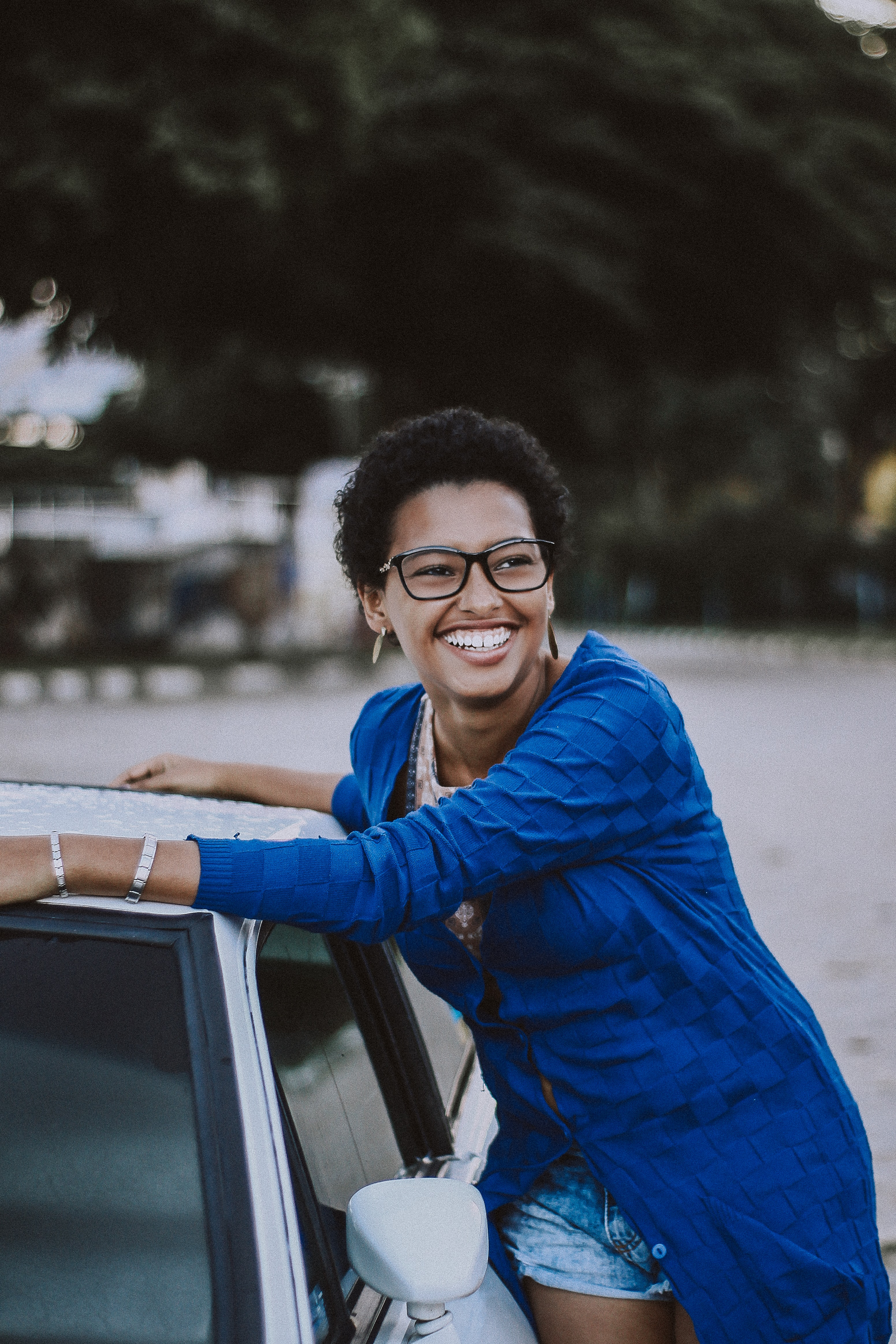 A smiling woman in glasses leaning against a car
